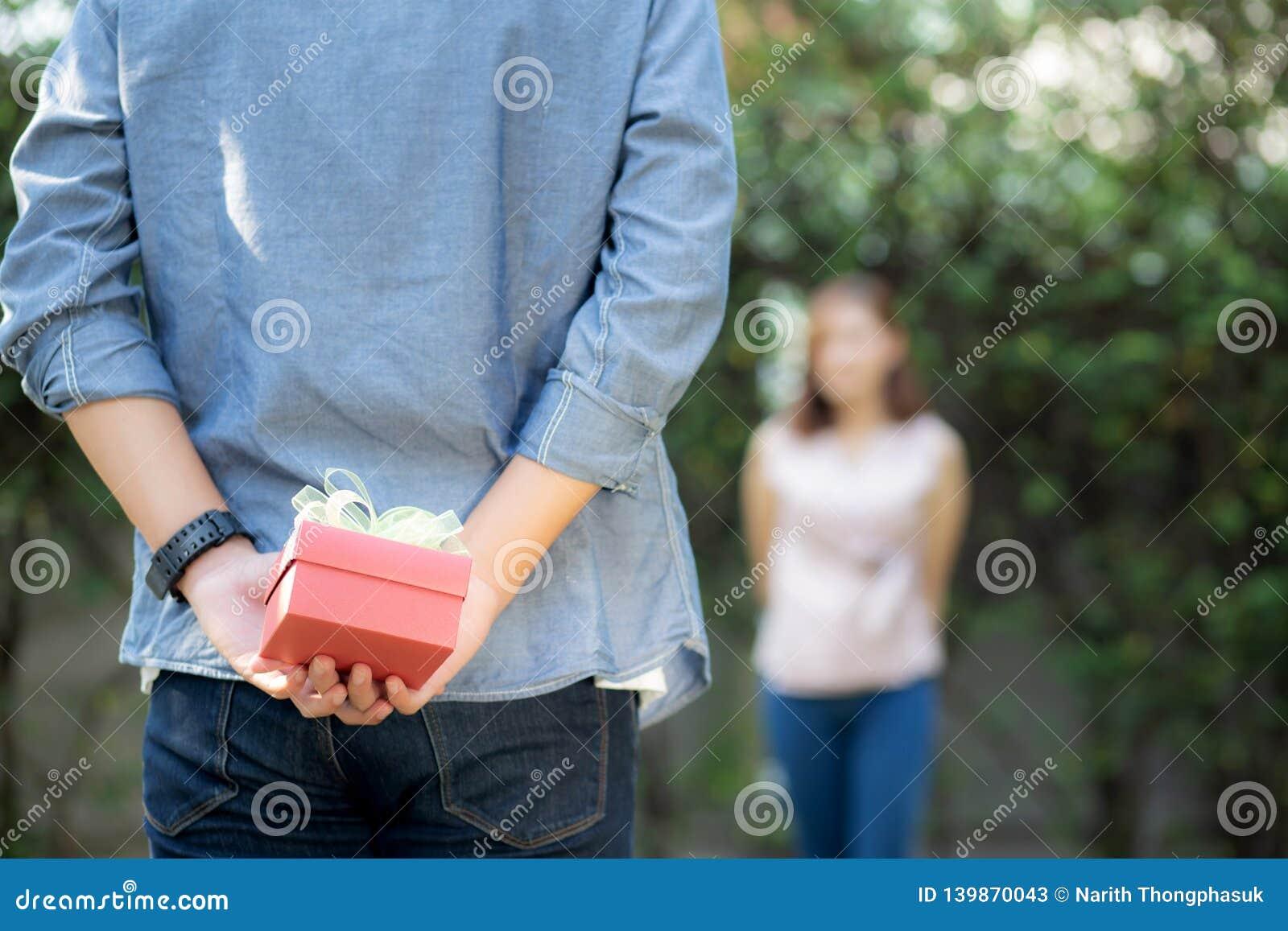 Junger asiatischer Mann, der hinter der hinteren Geschenkboxüberraschungsfreundin aufgeregt im Garten mit glücklichem, Jahrestags
