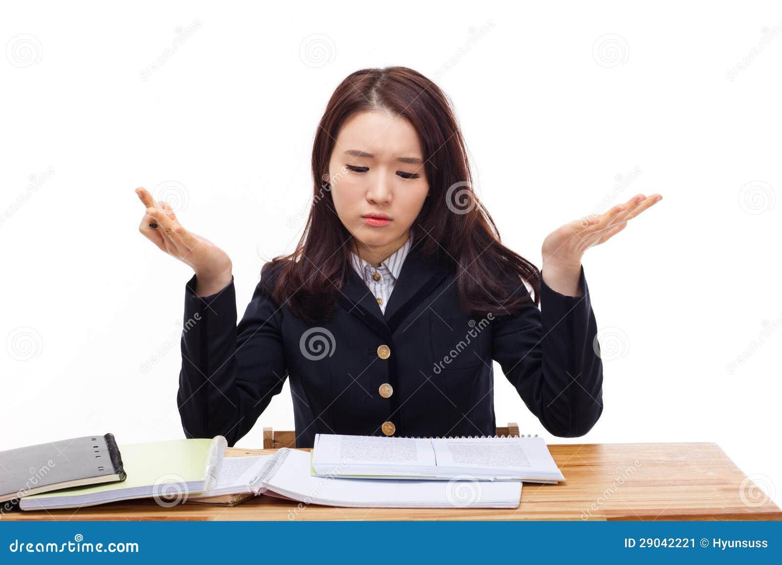 Junger asiatischer Student, der Problem auf Schreibtisch hat.