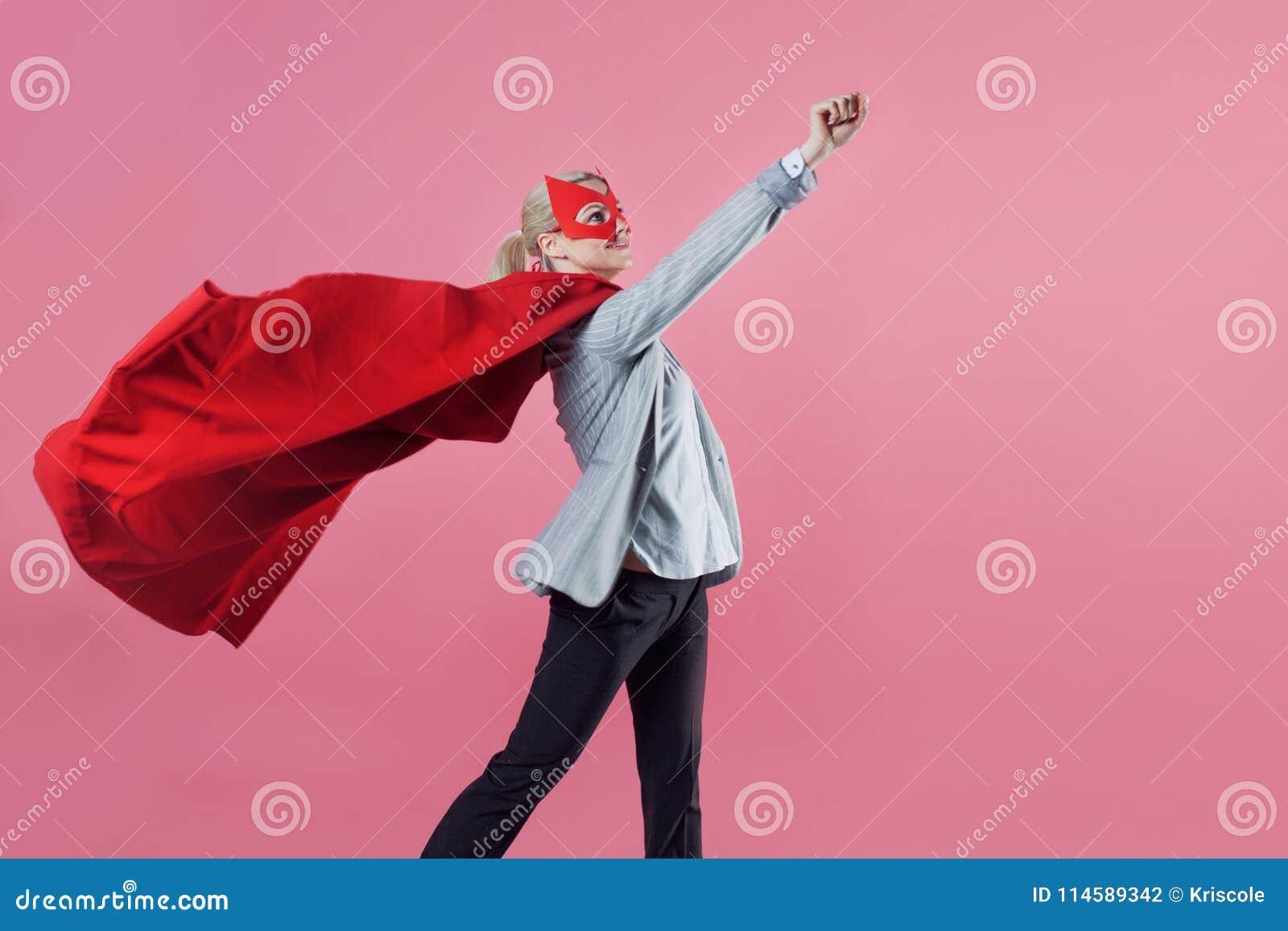 Junger attraktiver Frauensuperheld Mädchen in einem Anzug und eine Maske mit rotem Mantel des Helden