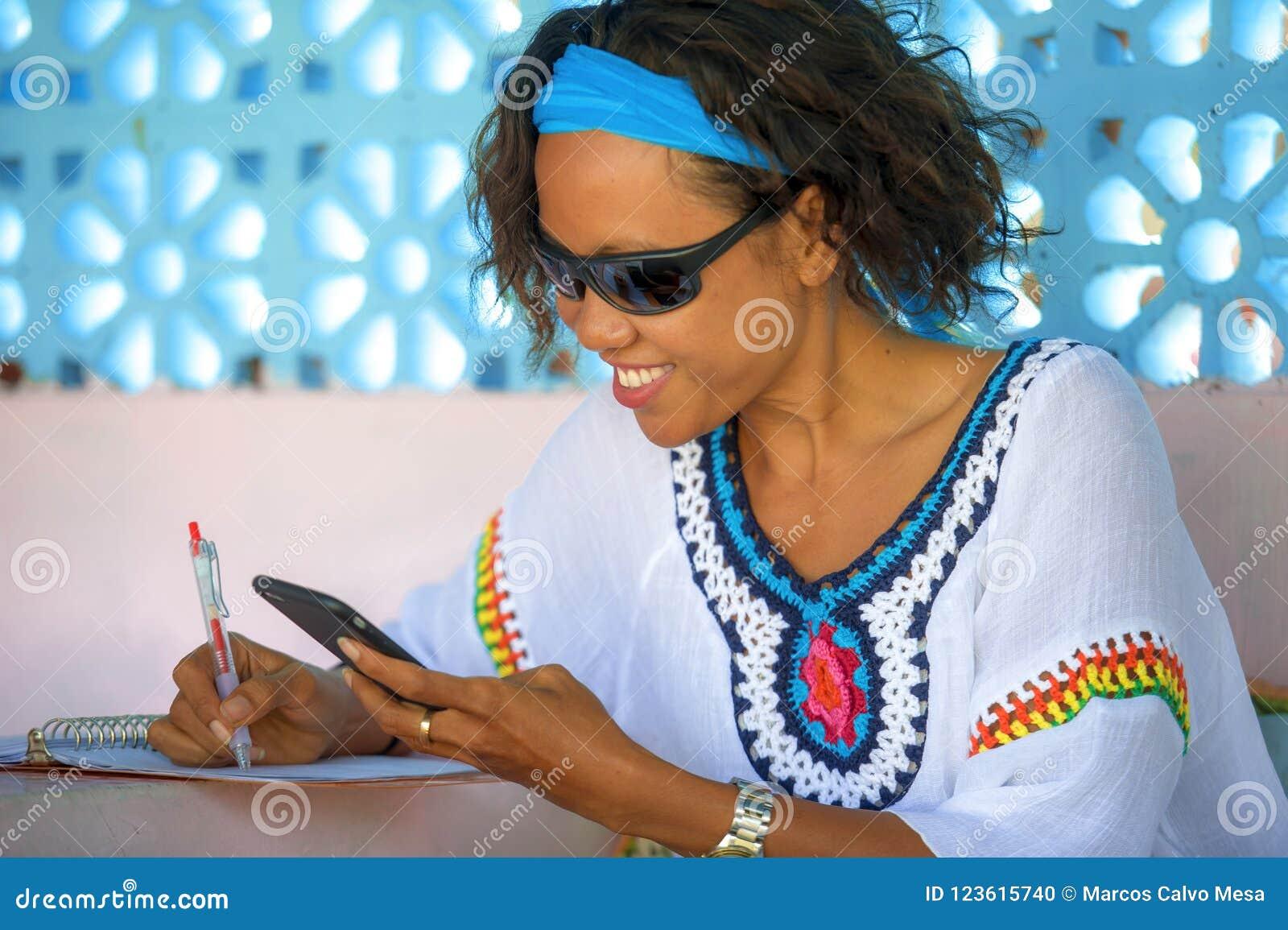 Junger attraktiver Hippie und exotisches schauendes Mädchen glücklich und entspannt unter Verwendung des Internet-Social Media, d