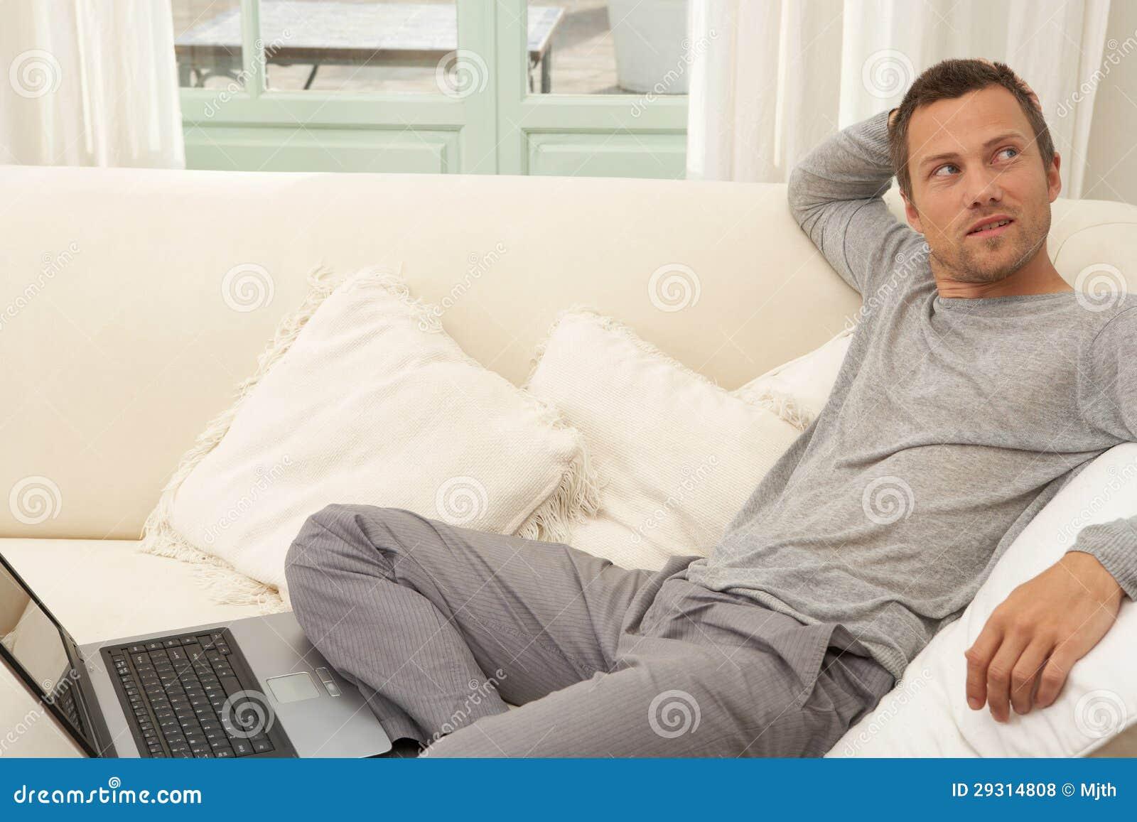 Laptop computer beim auf einem weißen sofa zu hause sitzen verwendet