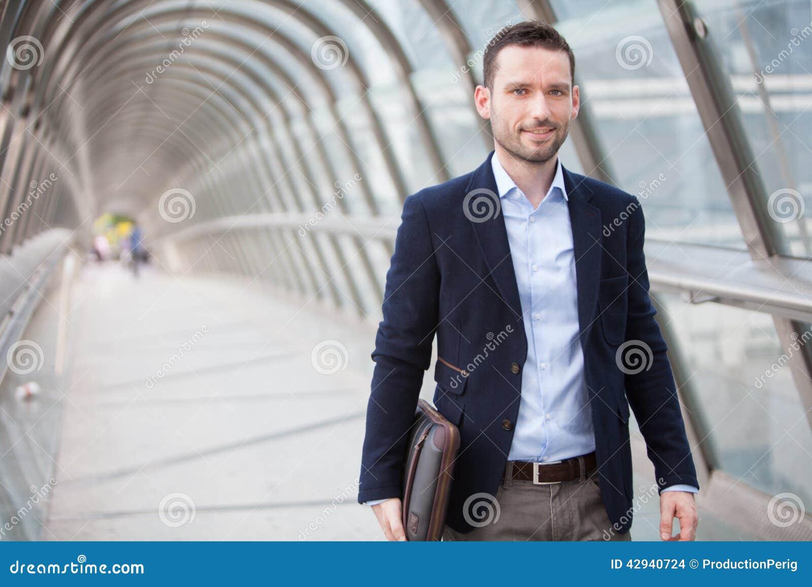 Junger attraktiver Mann, der in eine Flughafenhalle geht