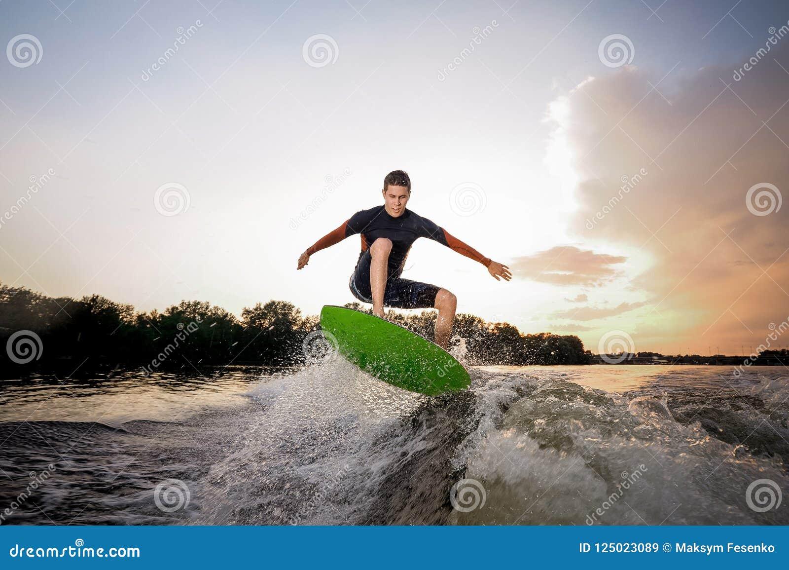 Junger attraktiver Mann, der einen Sprung auf dem grünen wakeboard macht