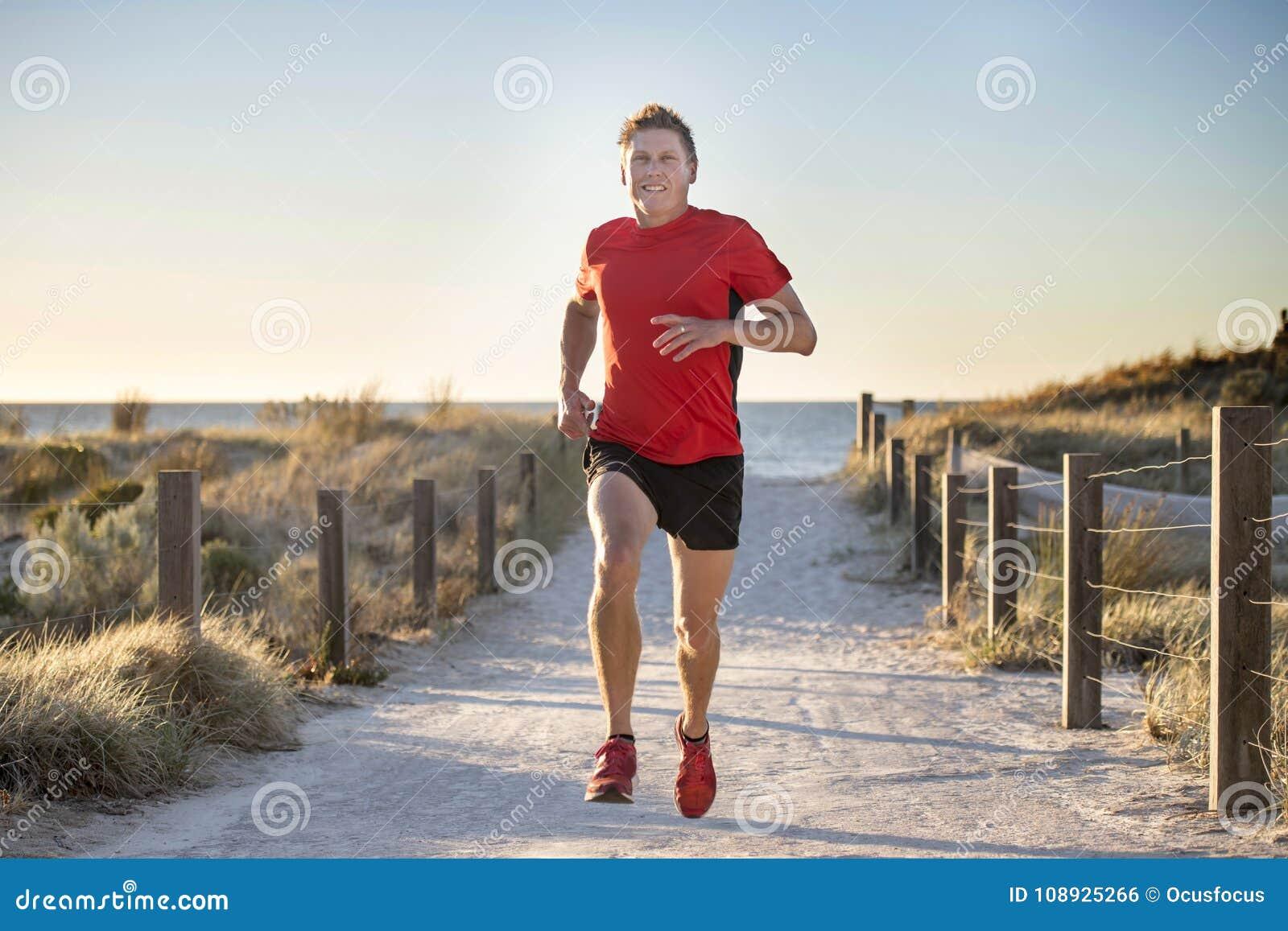 Junger attraktiver und glücklicher Sportläufermann mit Sitz und starkem gesundem Körpertraining auf weg von Straßenbahn in laufen