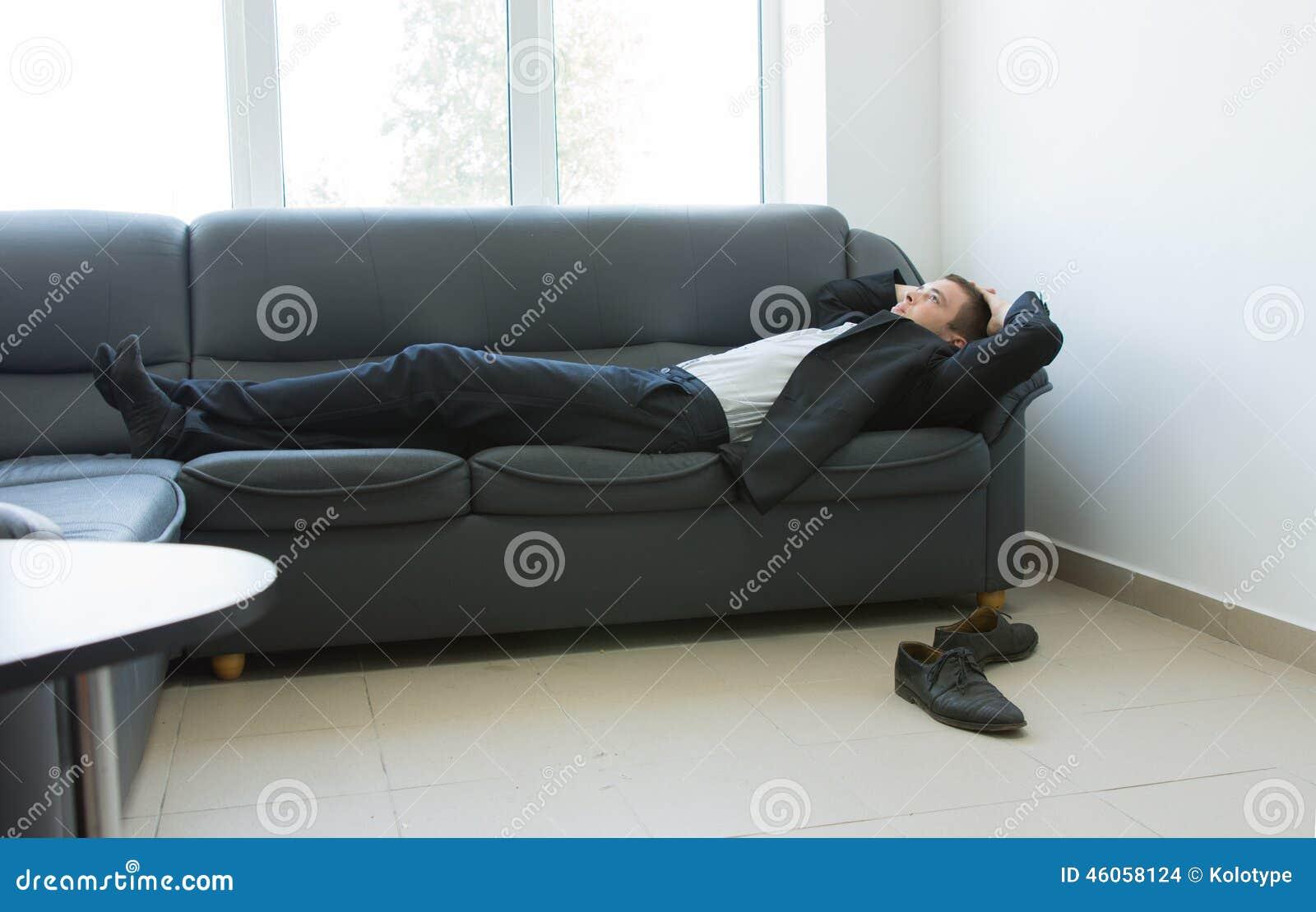 Junger Buro Mann Der Auf Couch Wahrend Des Bruches Liegt Stockfoto