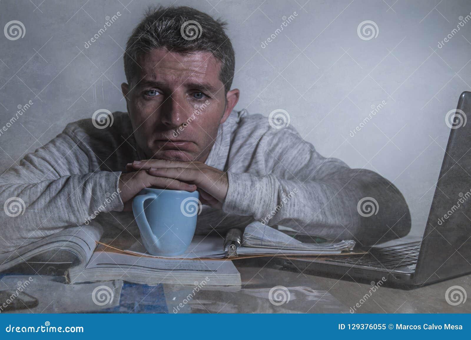 Junger besorgter und deprimierter Mann, der zu Hause Spät- Schreibtisch mit der glaubenden Laptop-Computer frustriertes und müdes
