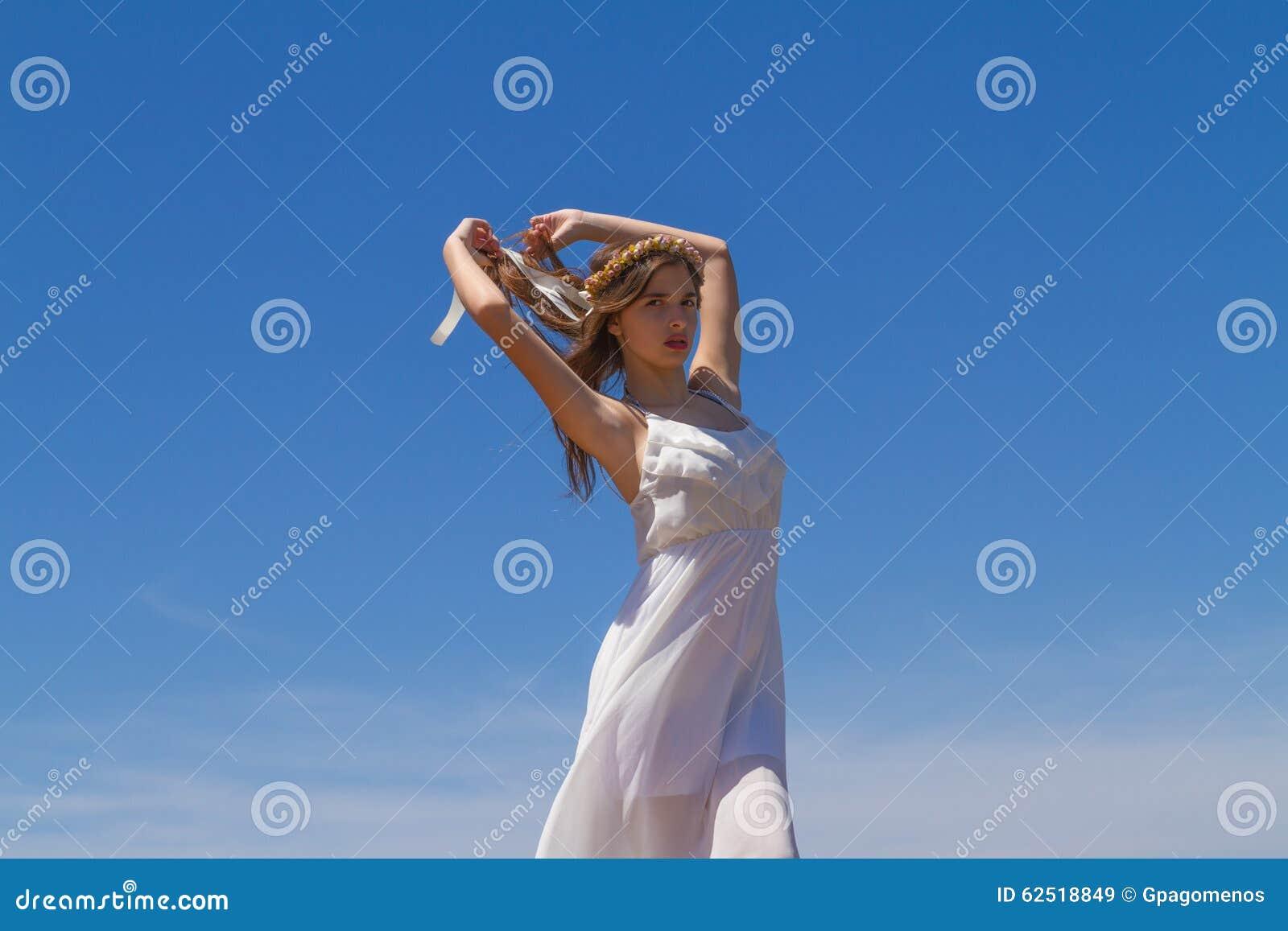 Junger Brunette im weißen schwachen Kleid