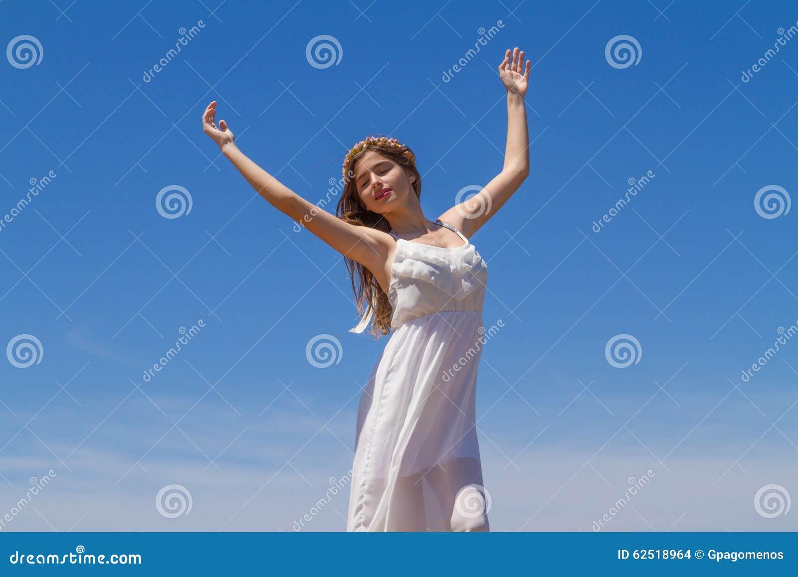 Junger Brunette im weißen schwachen Kleid genießt