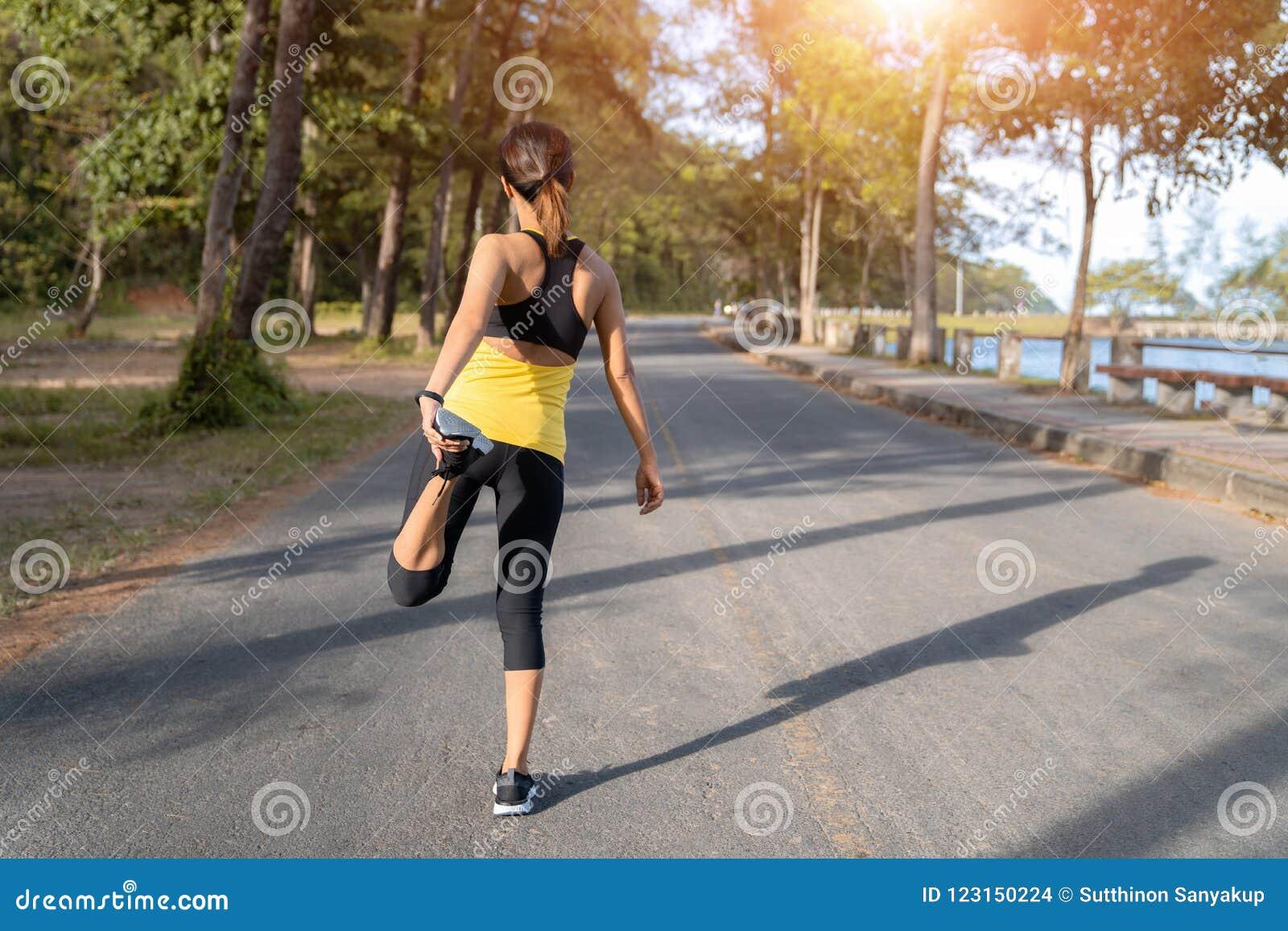 Junger Eignungsfrauenläufer, der Beine vor Lauf auf Stadt, junge Eignungssportfrau morgens läuft auf der Straße ausdehnt