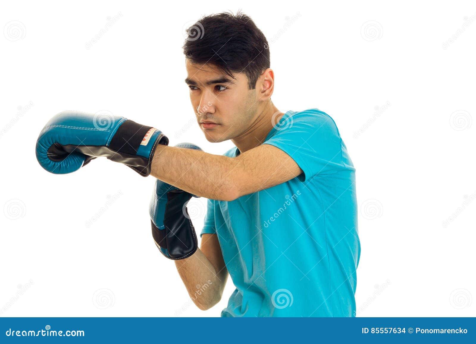 Junger ernster Brunettemann im blauen Boxhandschuhüben lokalisiert auf weißem Hintergrund