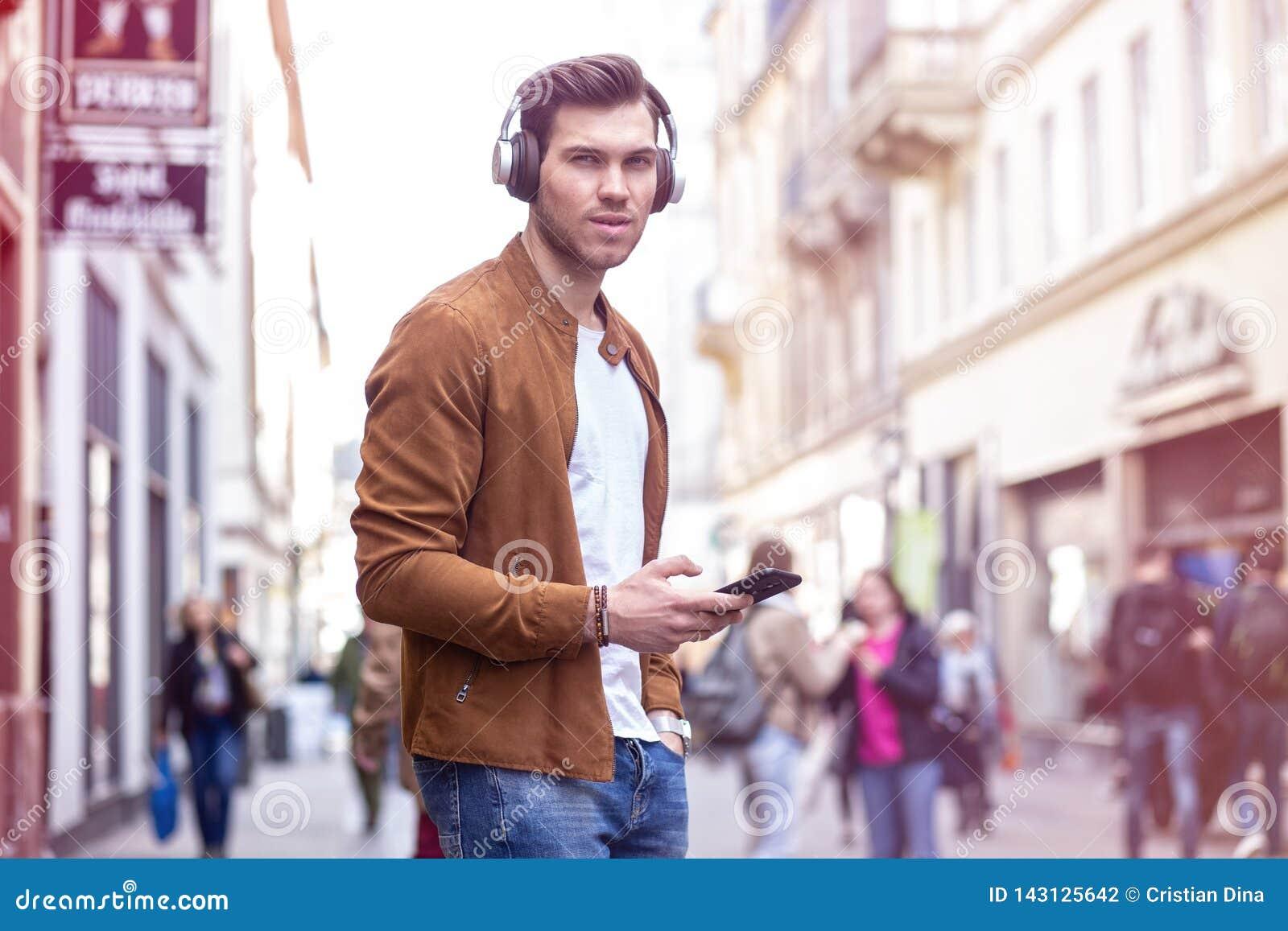 Junger erwachsener Mann-hörende Musik auf Smartphone und Kopfhörer auf der Straße zur Sommerzeit