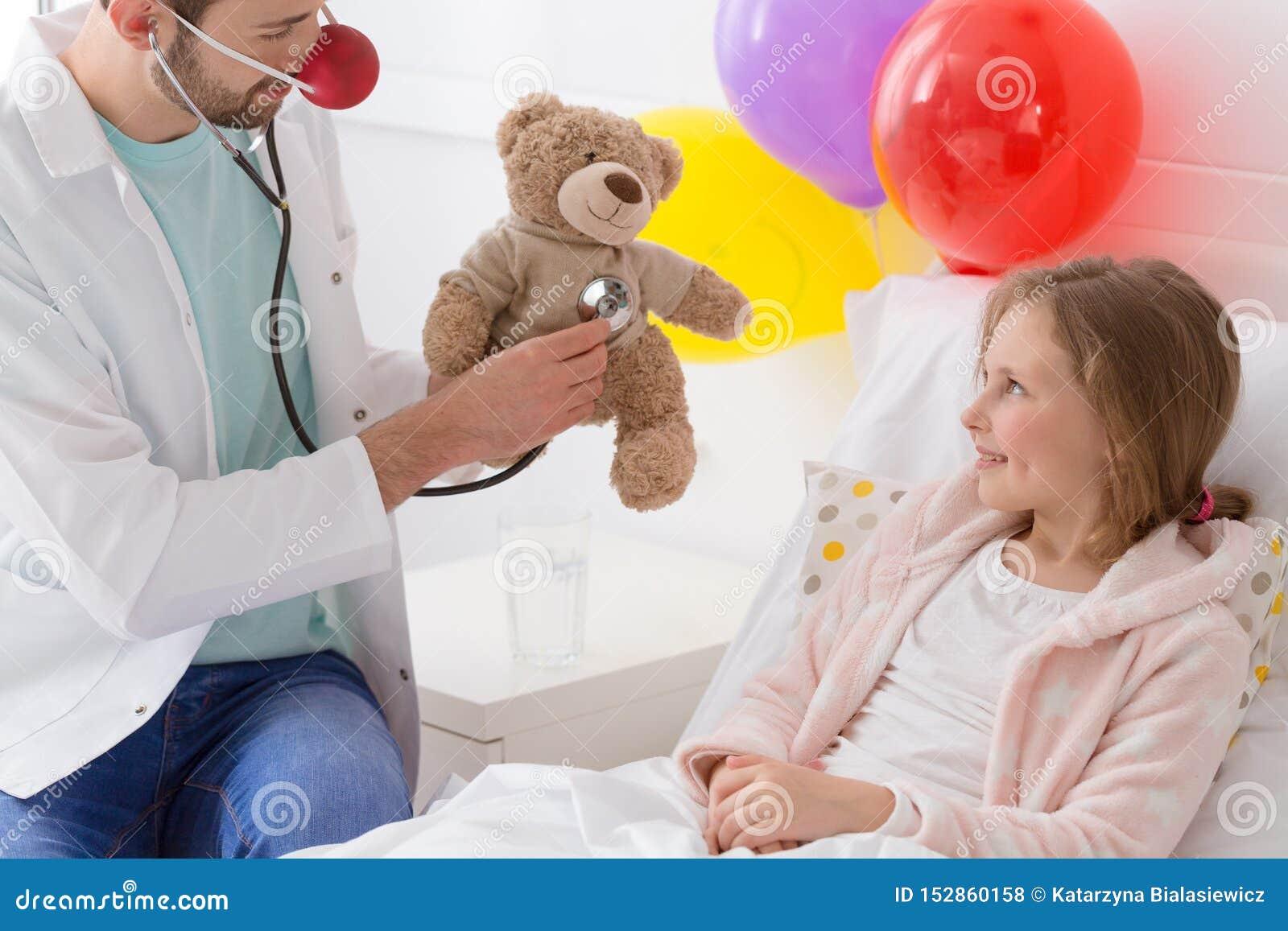 Junger Freiwilliger, der mit einem kranken Kind spielt