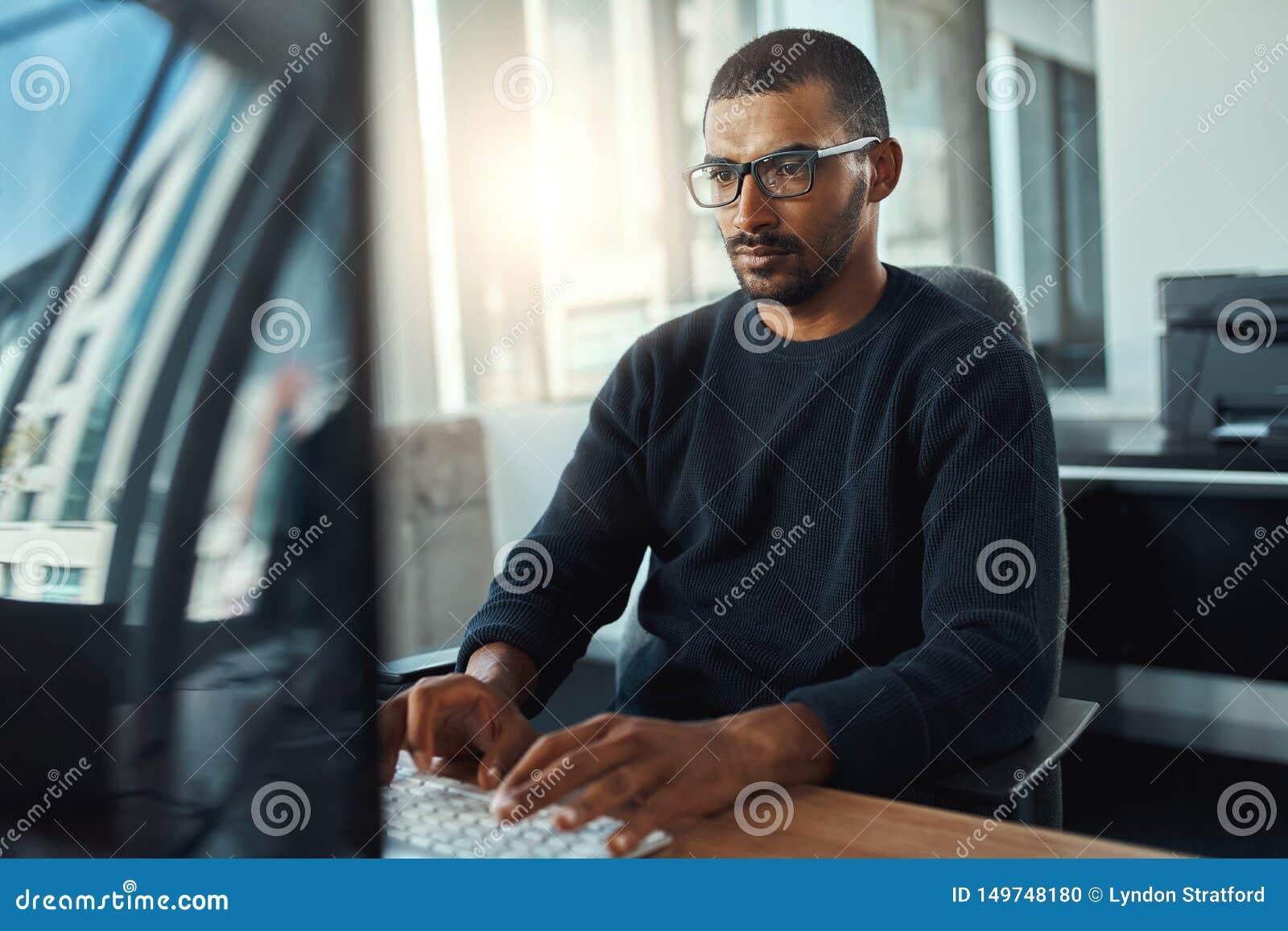 Junger Geschäftsmann, der am Arbeitsplatz arbeitet