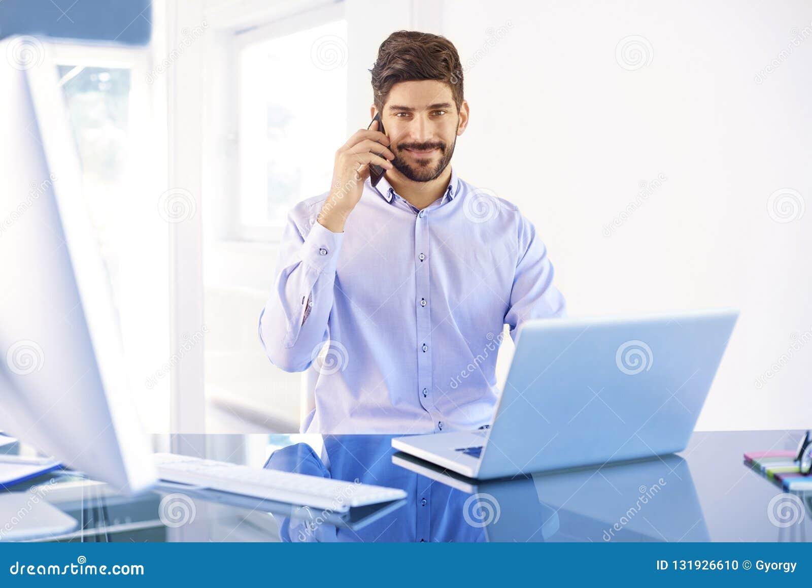 Junger Geschäftsmann, der einen Anruf beim Arbeiten auf Laptop macht