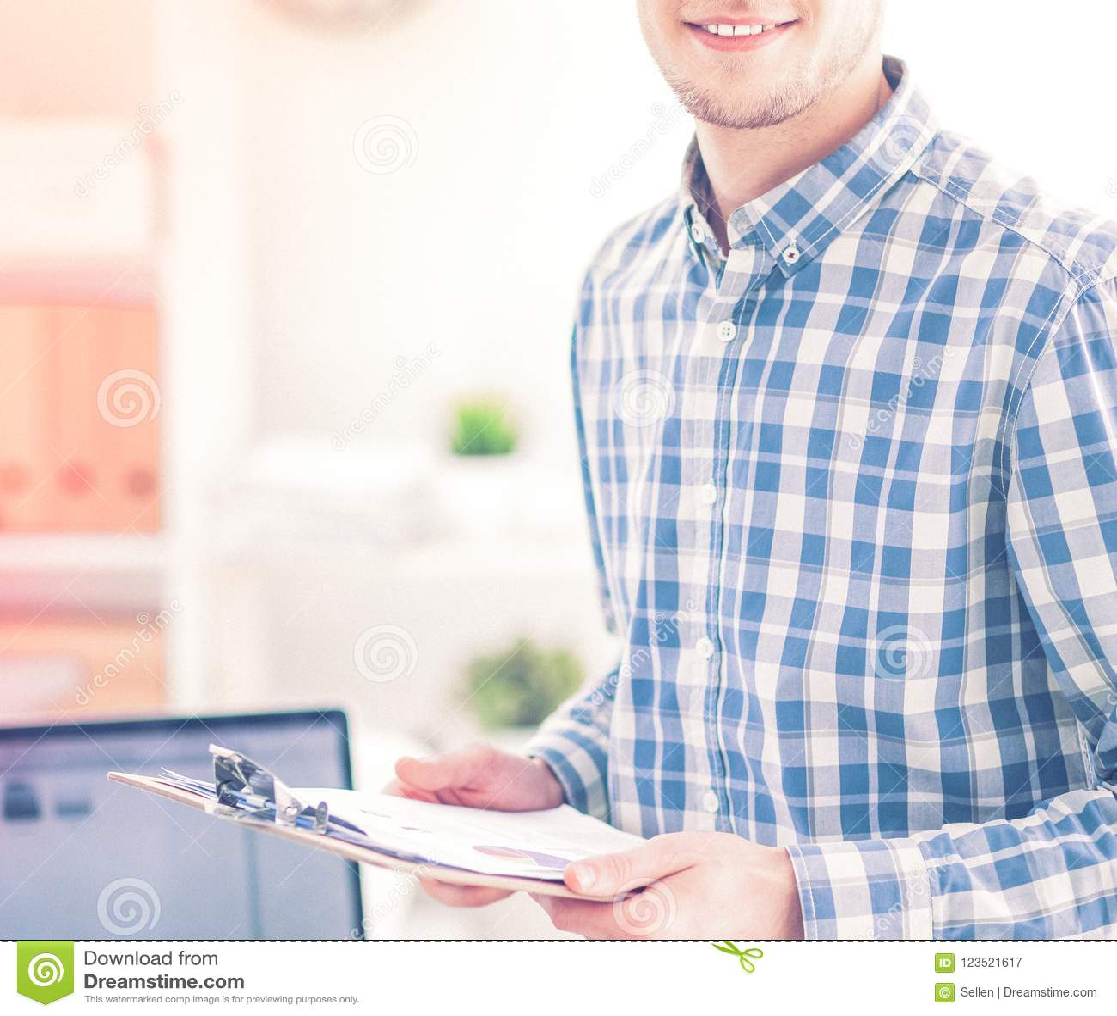 Junger Geschäftsmann, der im Büro, sitzend am Schreibtisch arbeitet