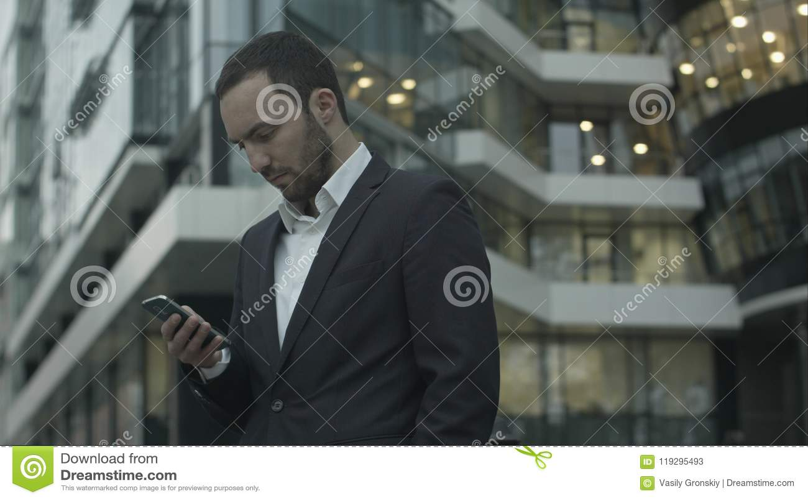 Junger Geschäftsmann liest eine Textnachricht, die außerhalb des Büros stehend ist