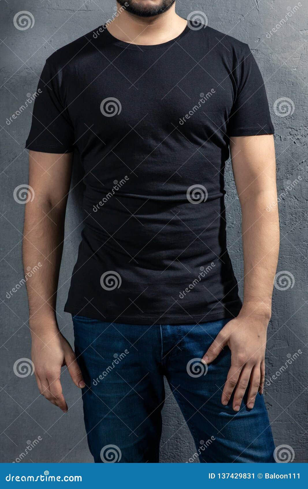 Junger gesunder Mann mit schwarzem T-Shirt auf konkretem Hintergrund