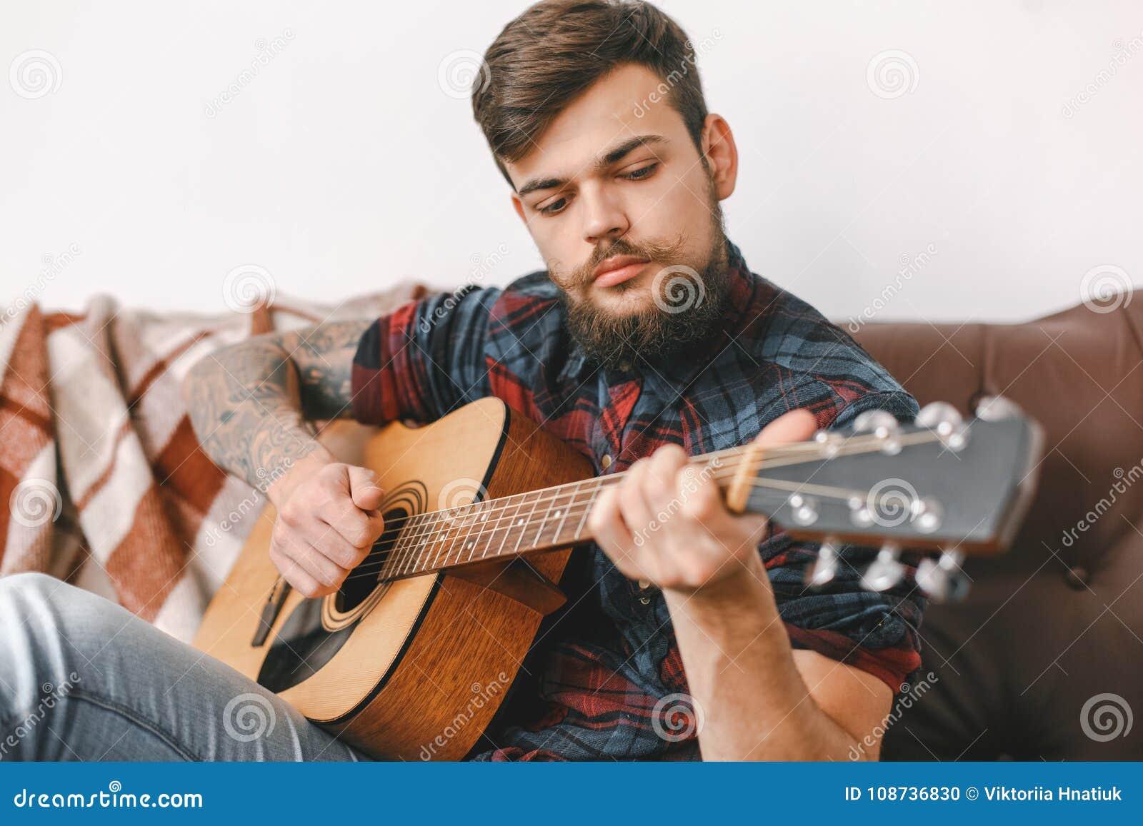 Junger Gitarristhippie zu Hause, der die Gitarre spielend ernst sitzt