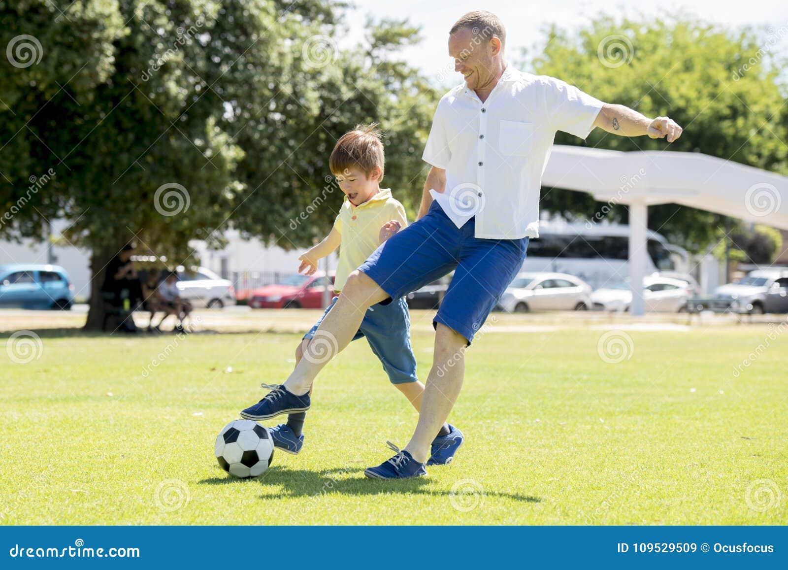 Junger glücklicher Vater und wenig aufgeregt 7 oder 8 Jahre alte Sohn, die zusammen Fußballfußball auf dem Stadtparkgarten läuft