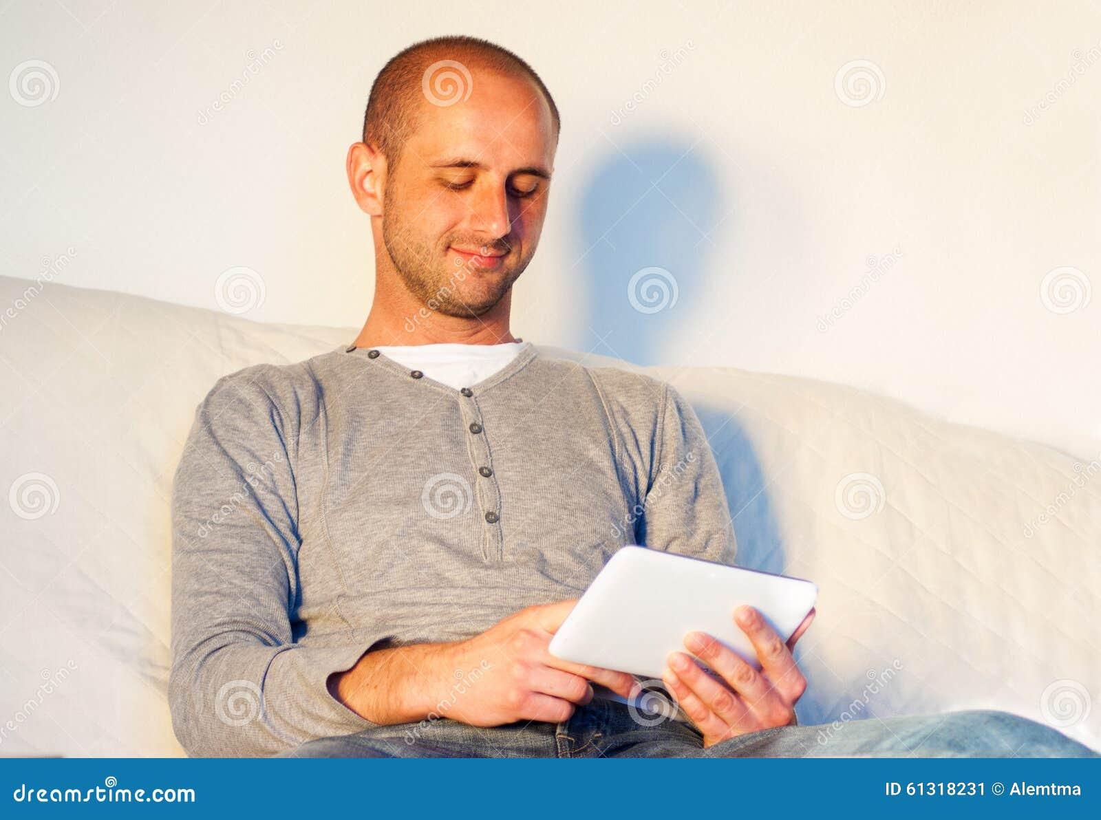 Junger gutaussehender Mann mit der Tablette, die auf Sofa sich entspannt