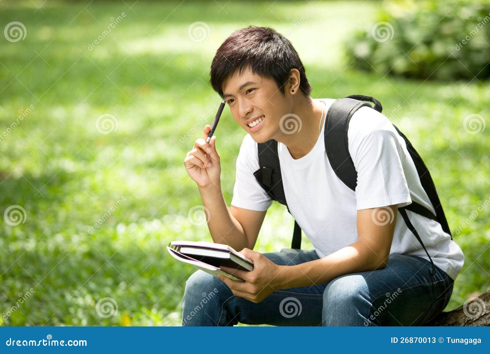 Junger hübscher asiatischer student mit büchern und toothy lächeln