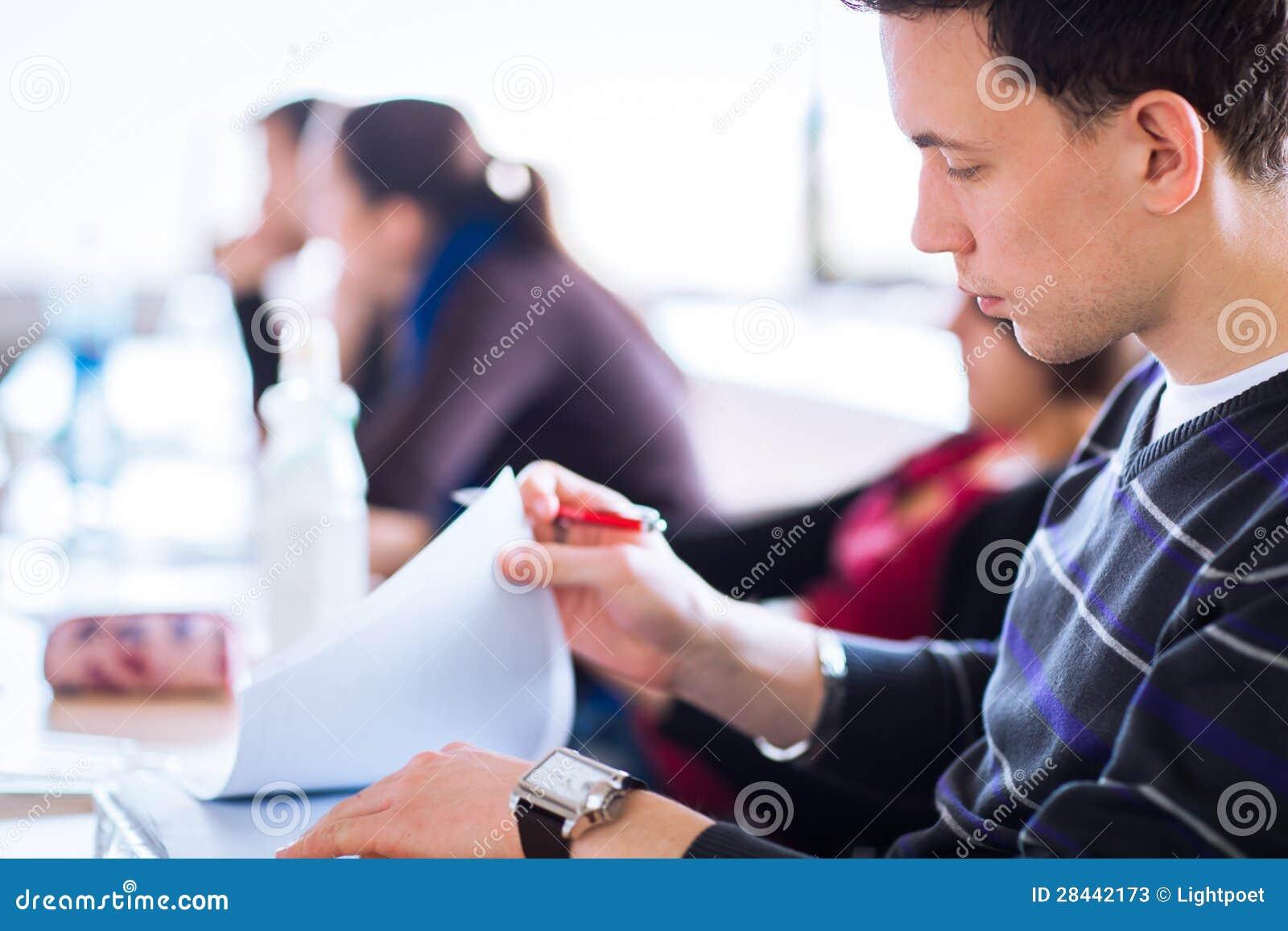 Junger, hübscher männlicher Student, der voll in einem Klassenzimmer sitzt