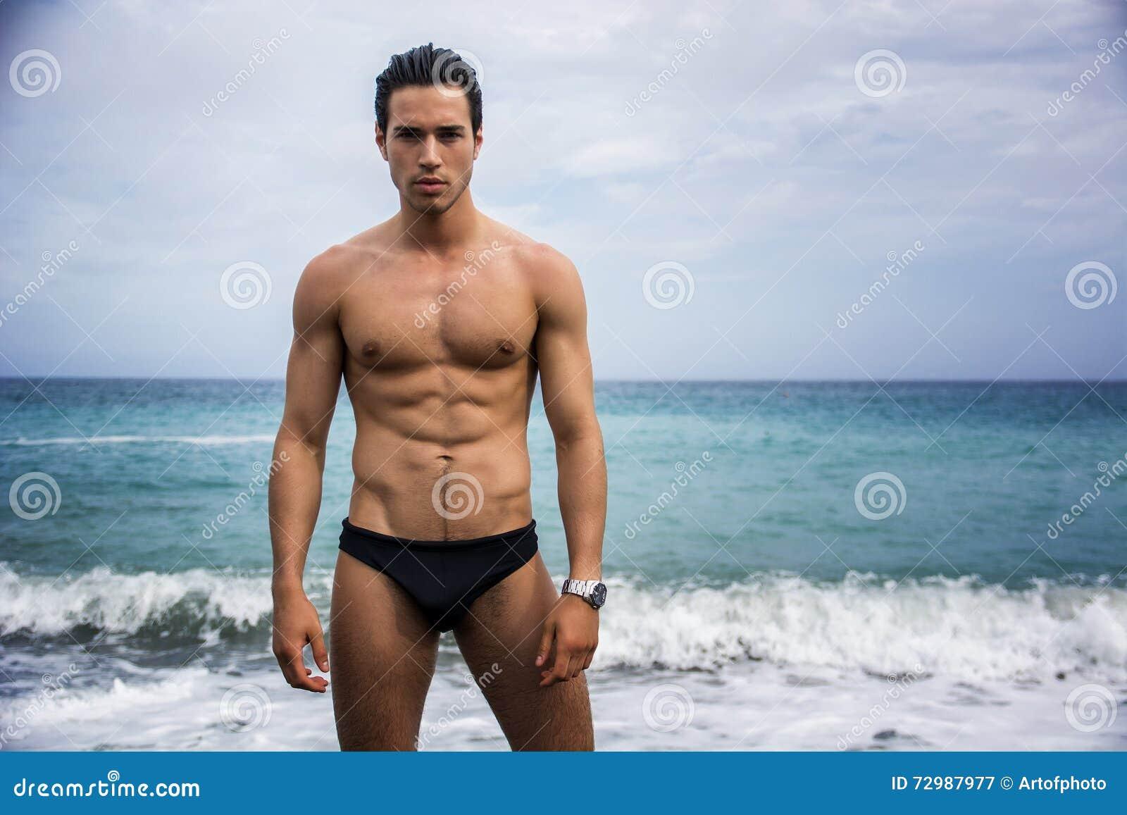 junger hemdloser athletischer mann der im wasser durch ozeanufer steht stockbild bild von. Black Bedroom Furniture Sets. Home Design Ideas