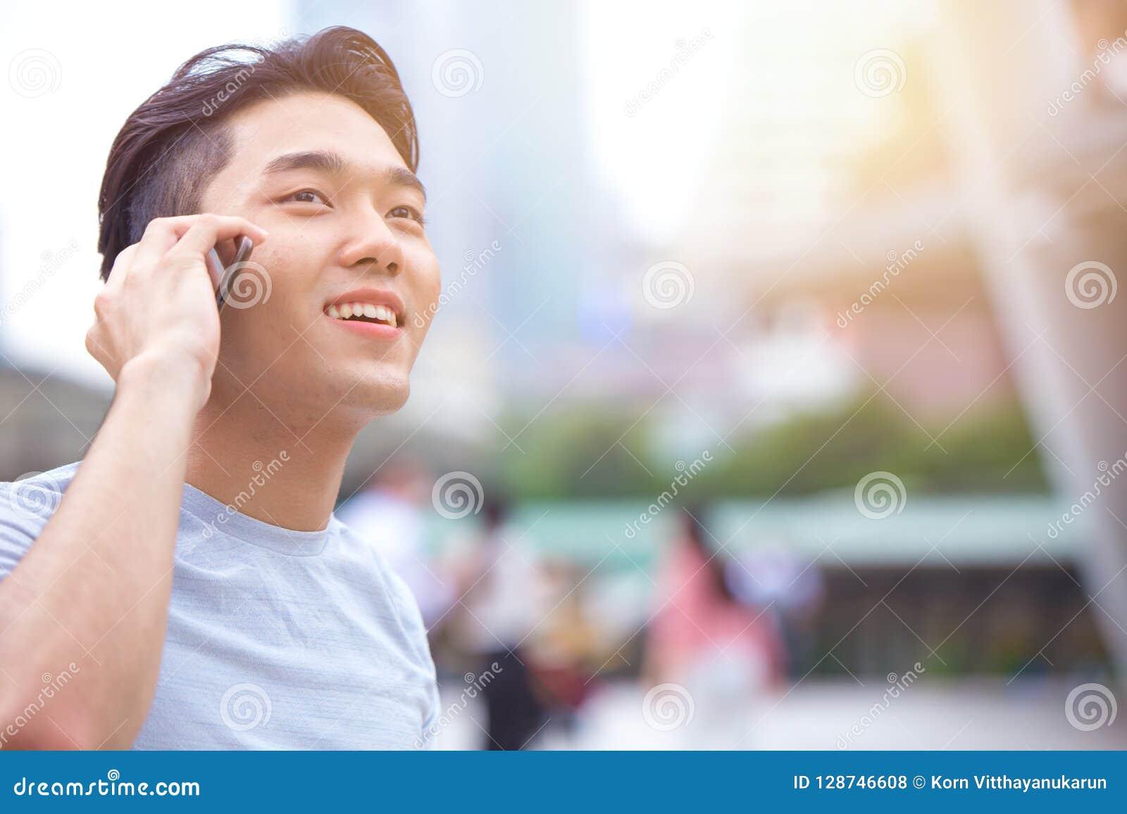 Junger intelligenter asiatischer männlicher jugendlich nennender Telefonanruf