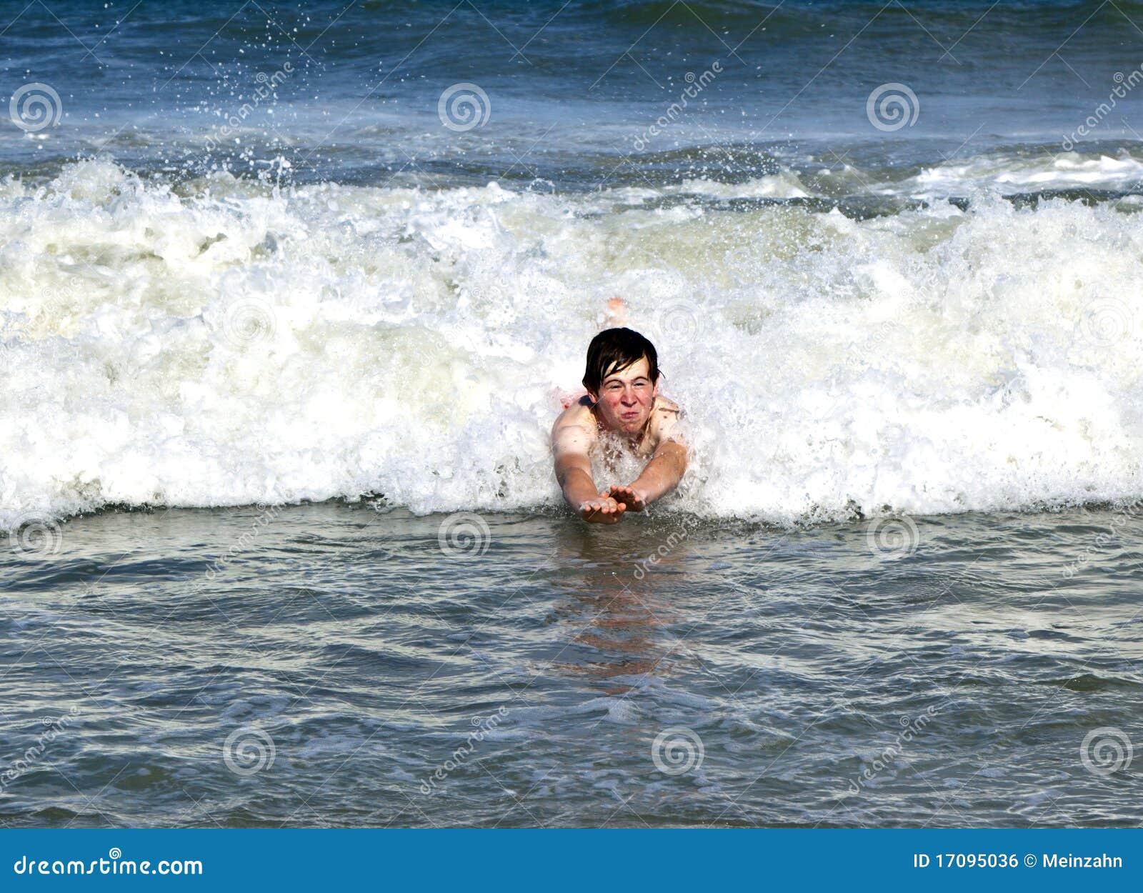 Junger Junge ist die Karosserie, die in die Wellen surft