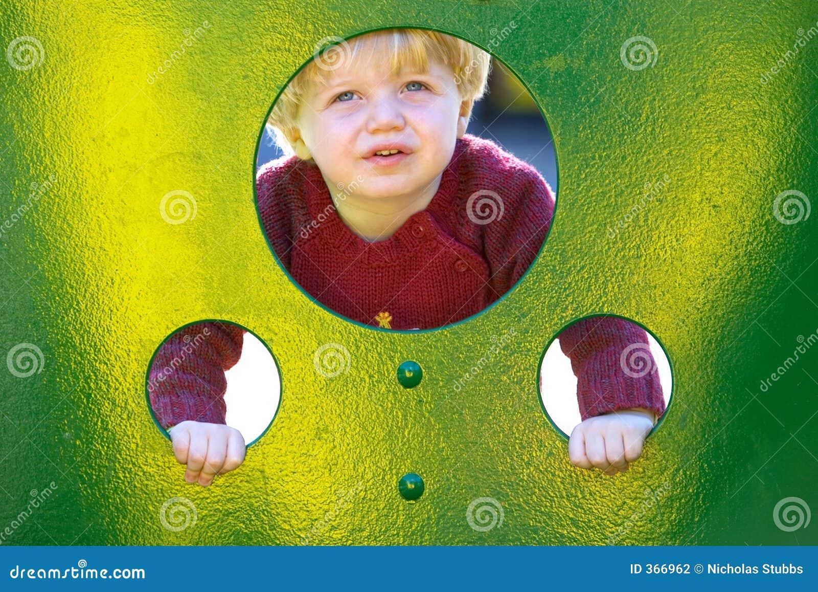 Junger Junge oder Kleinkind, die durch Löcher in einer Wand in einem Spielplatz schauen