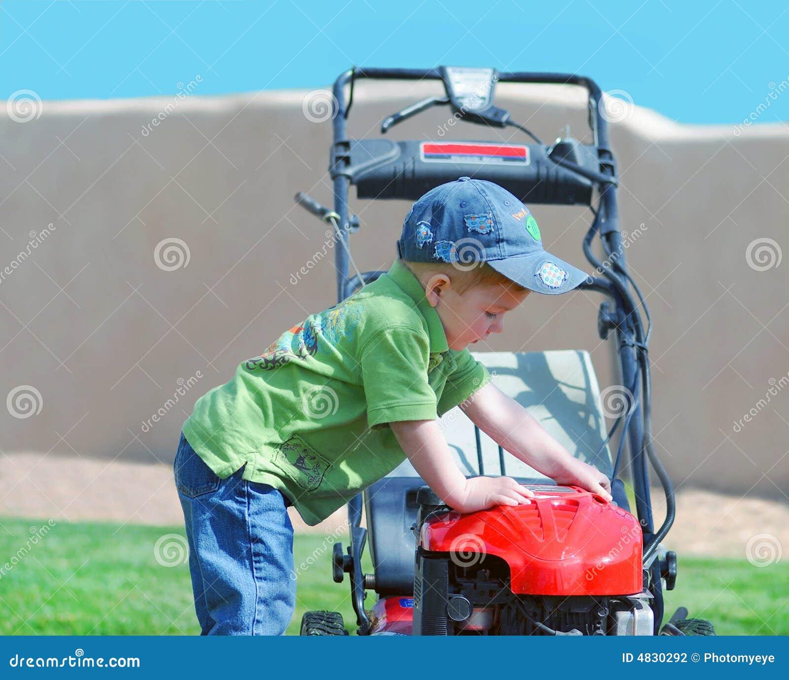 Junger Junge und Gartenmäher