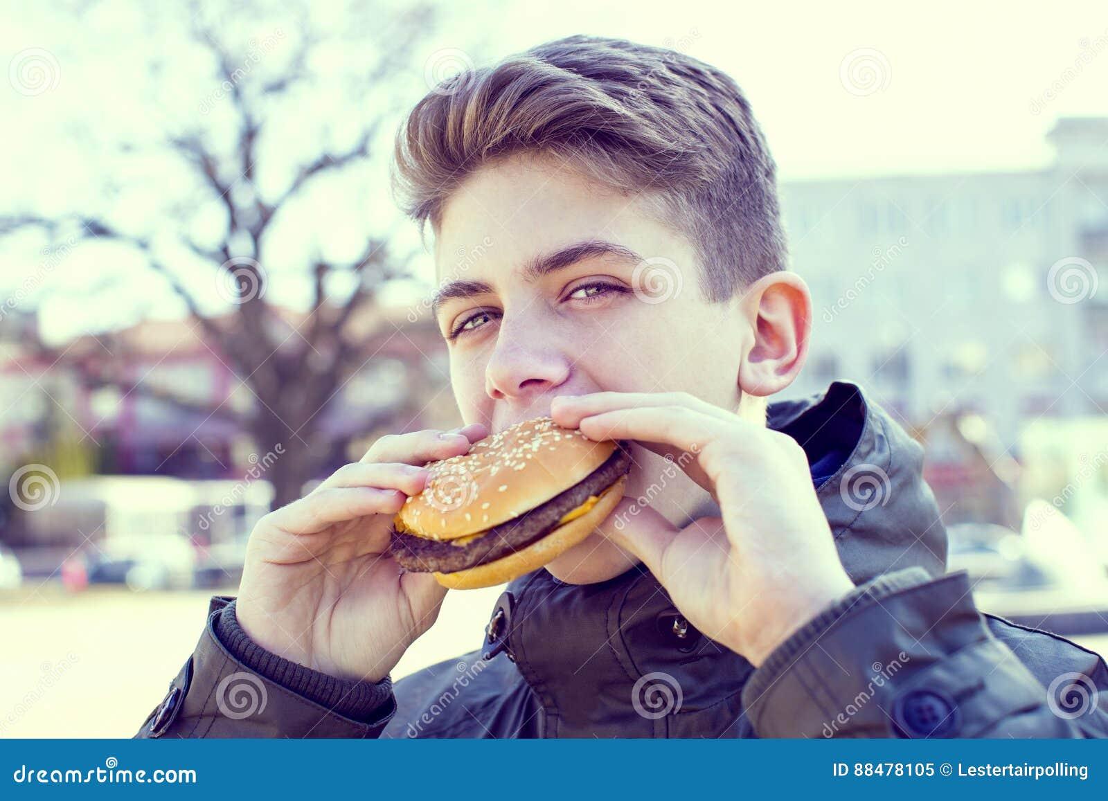 Junger Kerl, der einen Cheeseburger auf der Natur isst