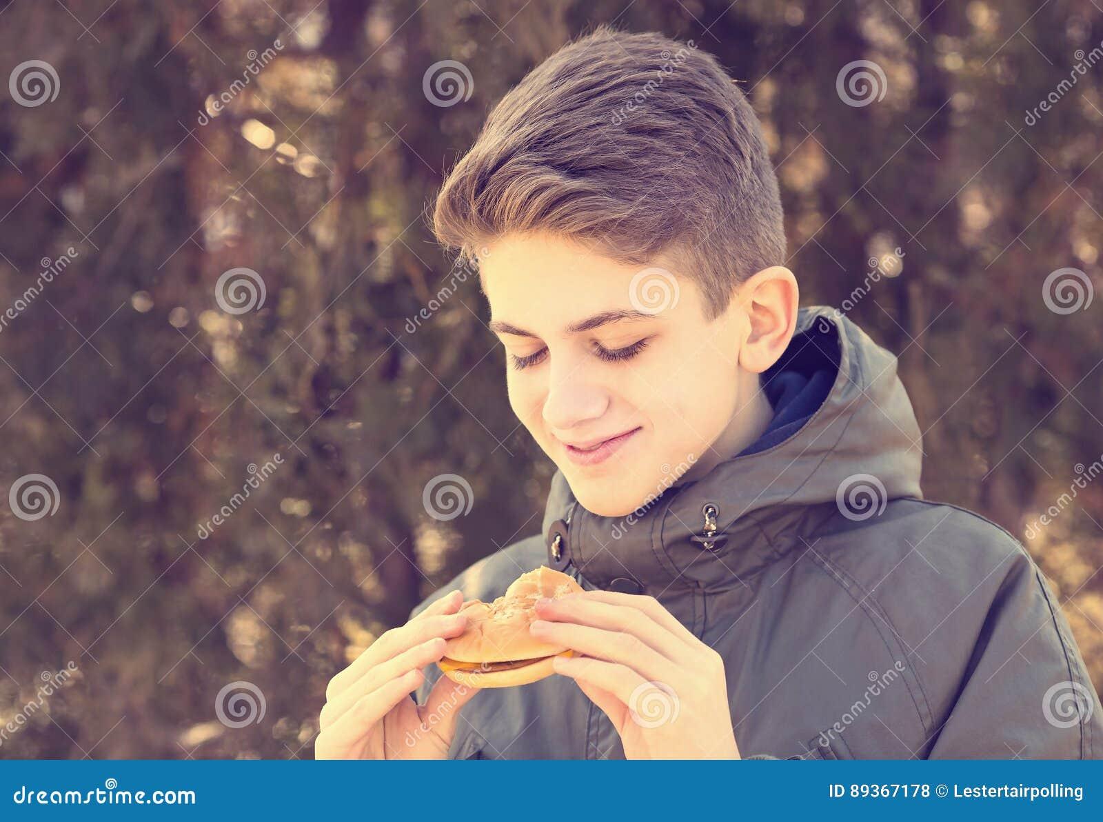 Junger Kerl, der einen Cheeseburger isst