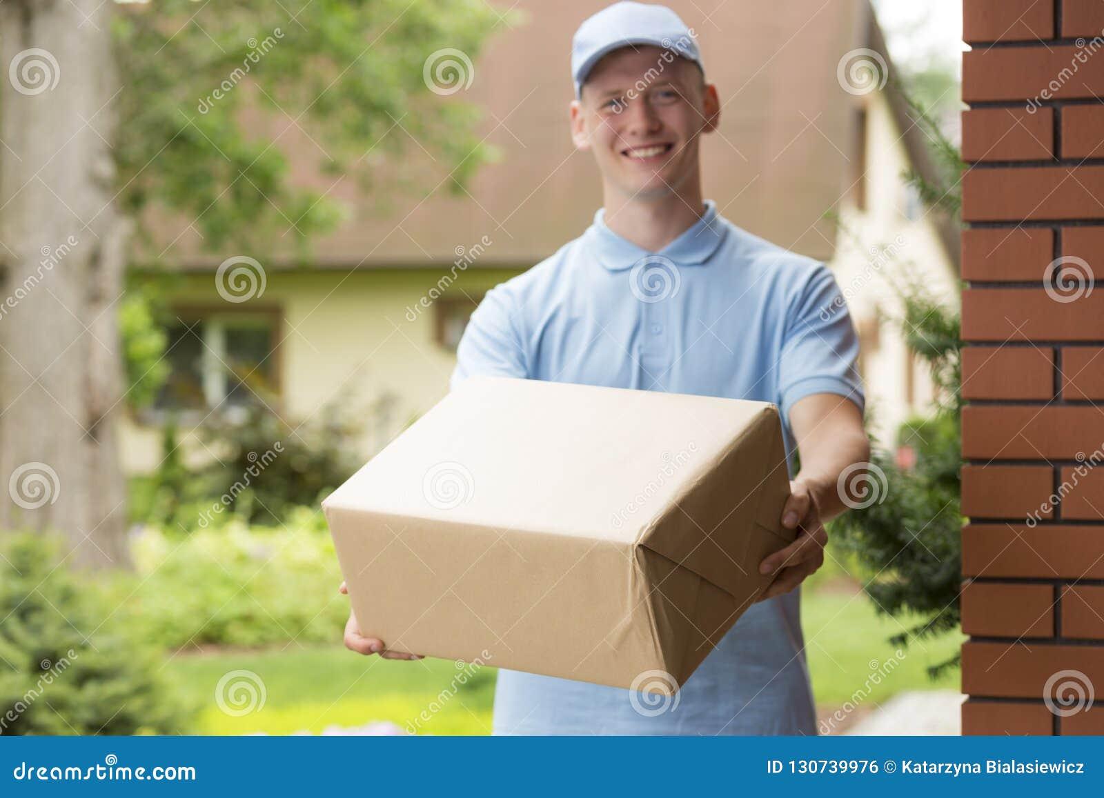 Junger Kurier in der blauen Uniform, die ein Paket hält