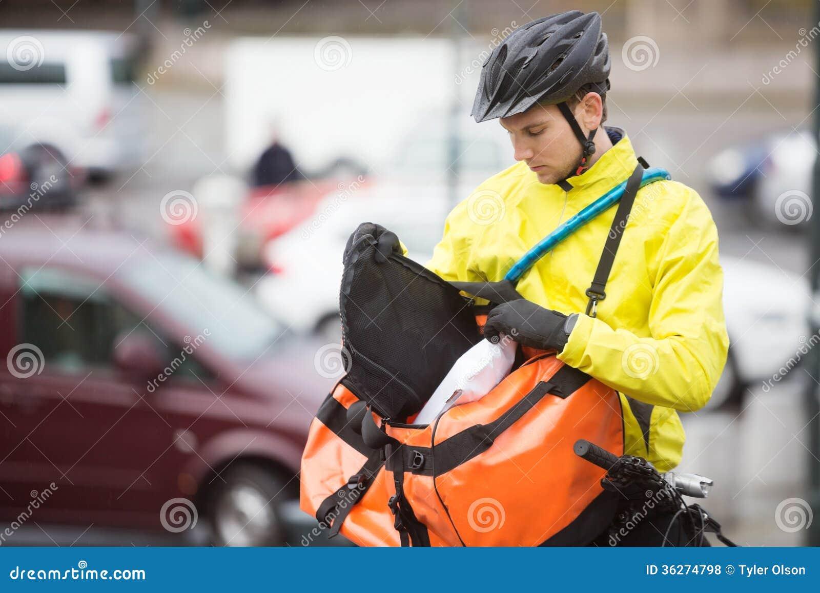 Junger männlicher Radfahrer, der Paket in Kurier Bag einsetzt