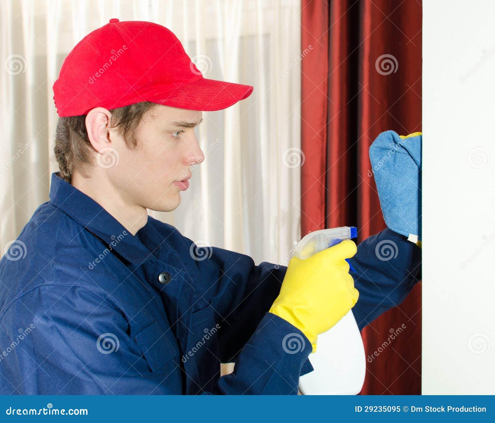 Junger männlicher Reiniger mit Hilfsmitteln.