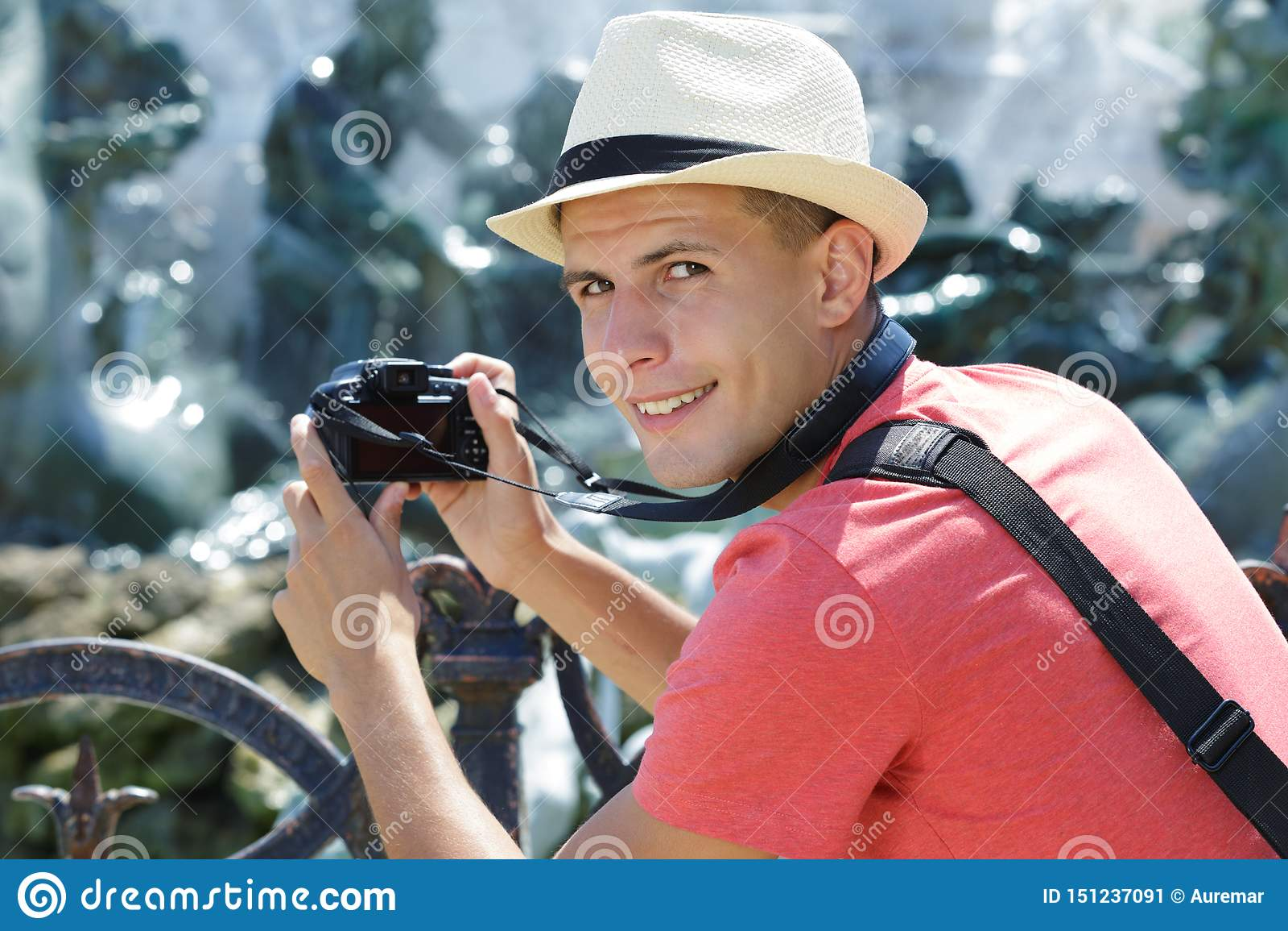 Junger männlicher Tourist, der Foto mit Digitalkamera macht