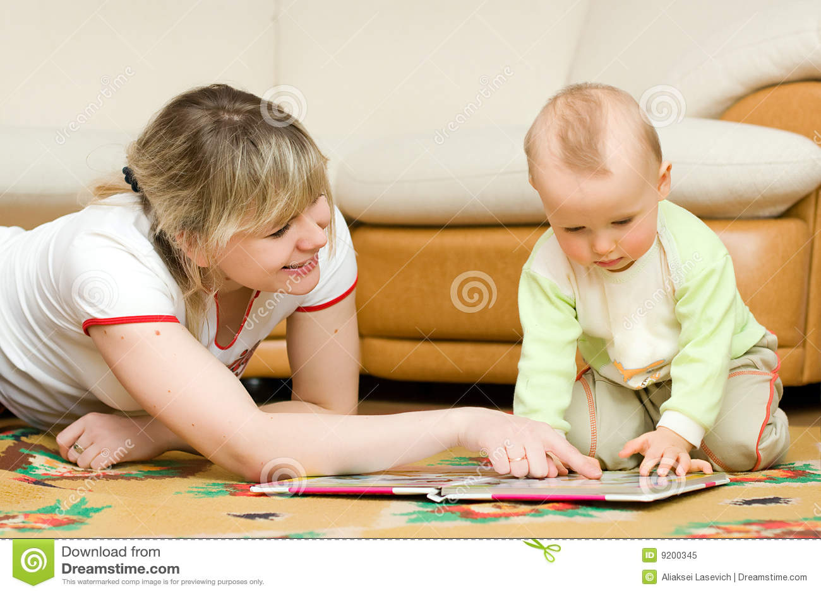 Junger Mammamesswert ihr kleines Sohnbuch auf einem Fußboden