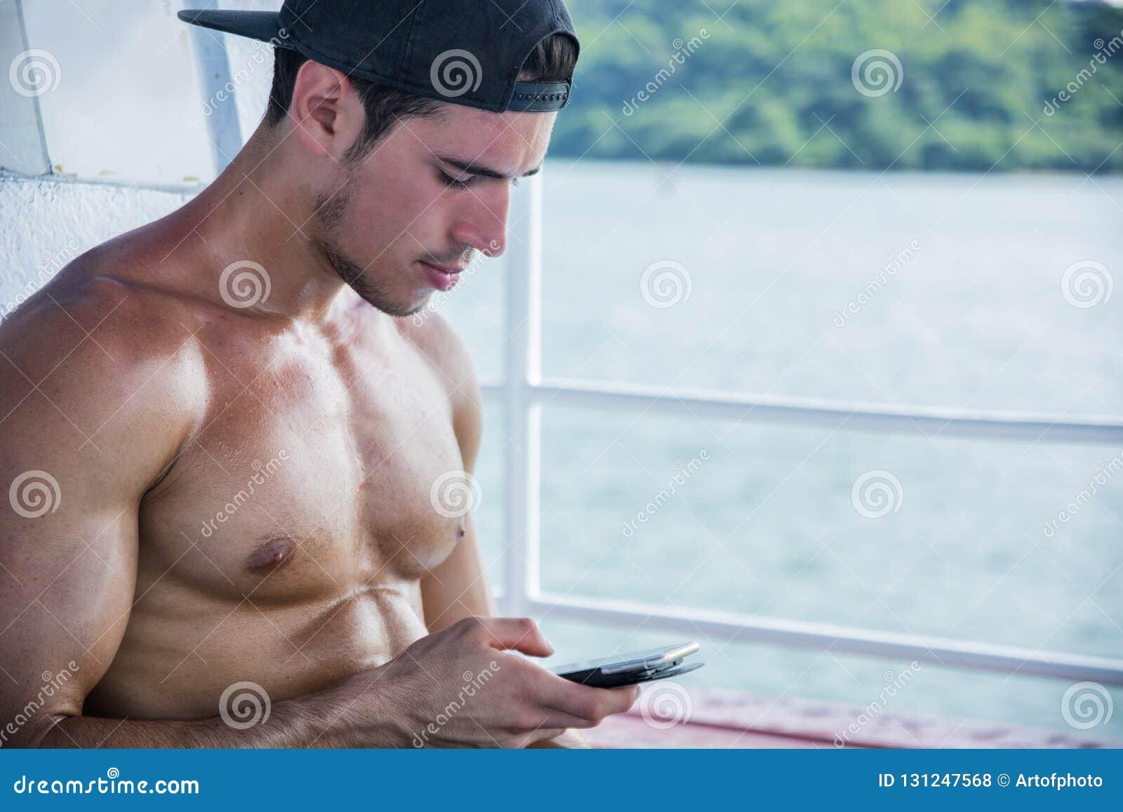 Junger Mann auf Boot unter Verwendung des Handys, hemdlos