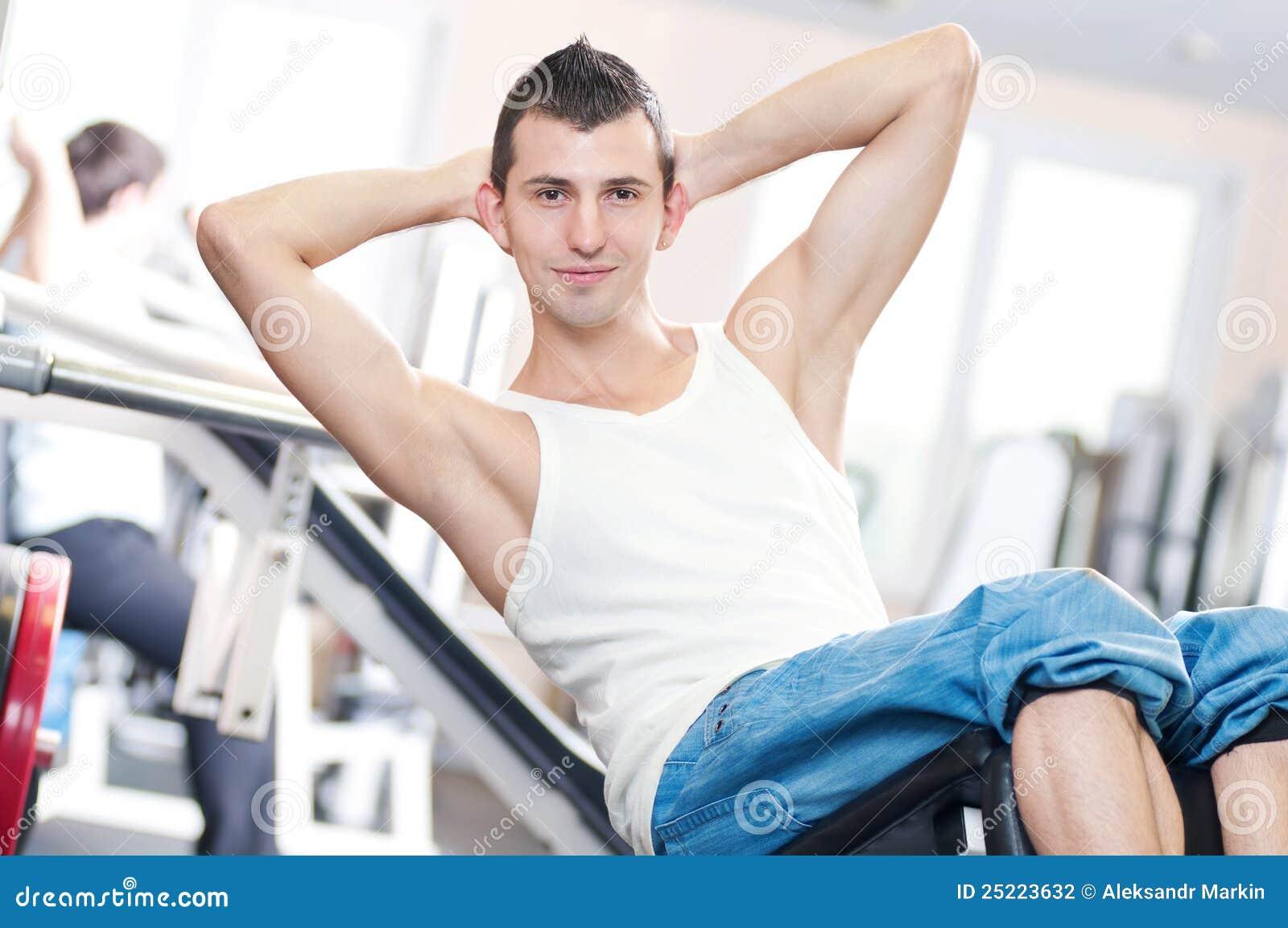 Junger Mann, der Übungen an der Gymnastik tut