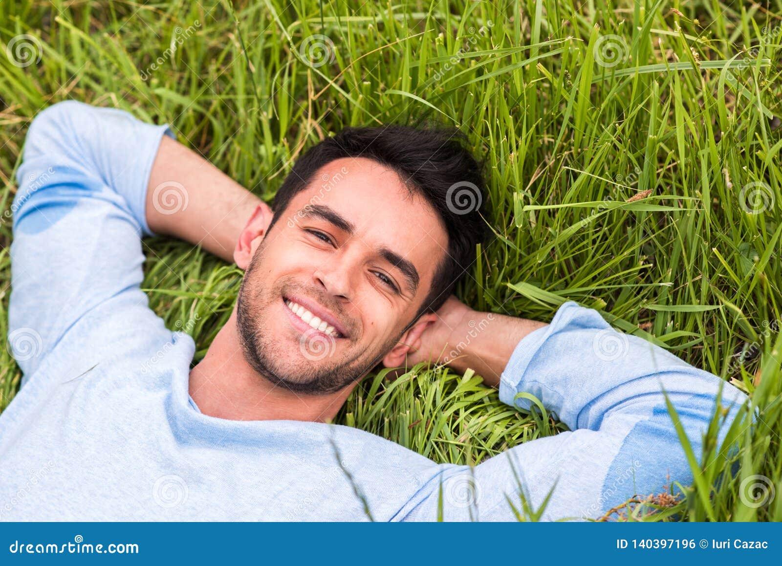 Junger Mann, der auf dem grünen träumenden Gras und die Kamera betrachten liegt relax