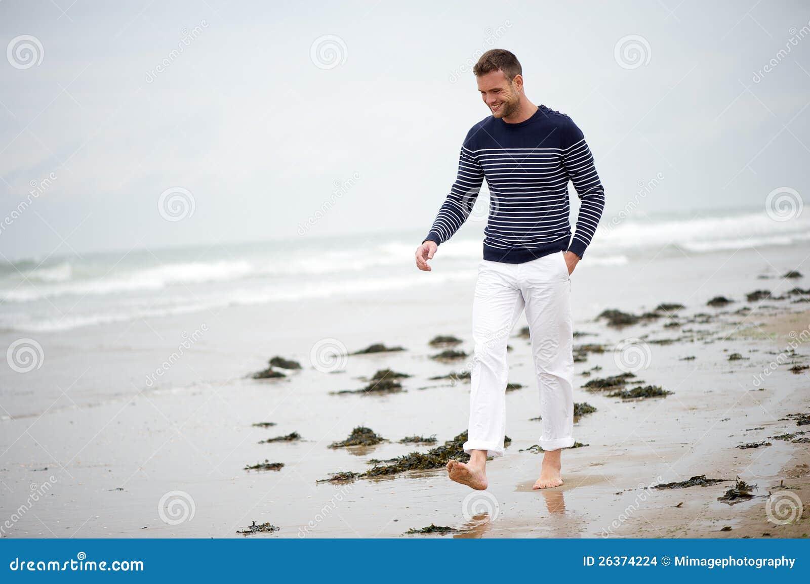 Junger Mann, der auf den Strand geht