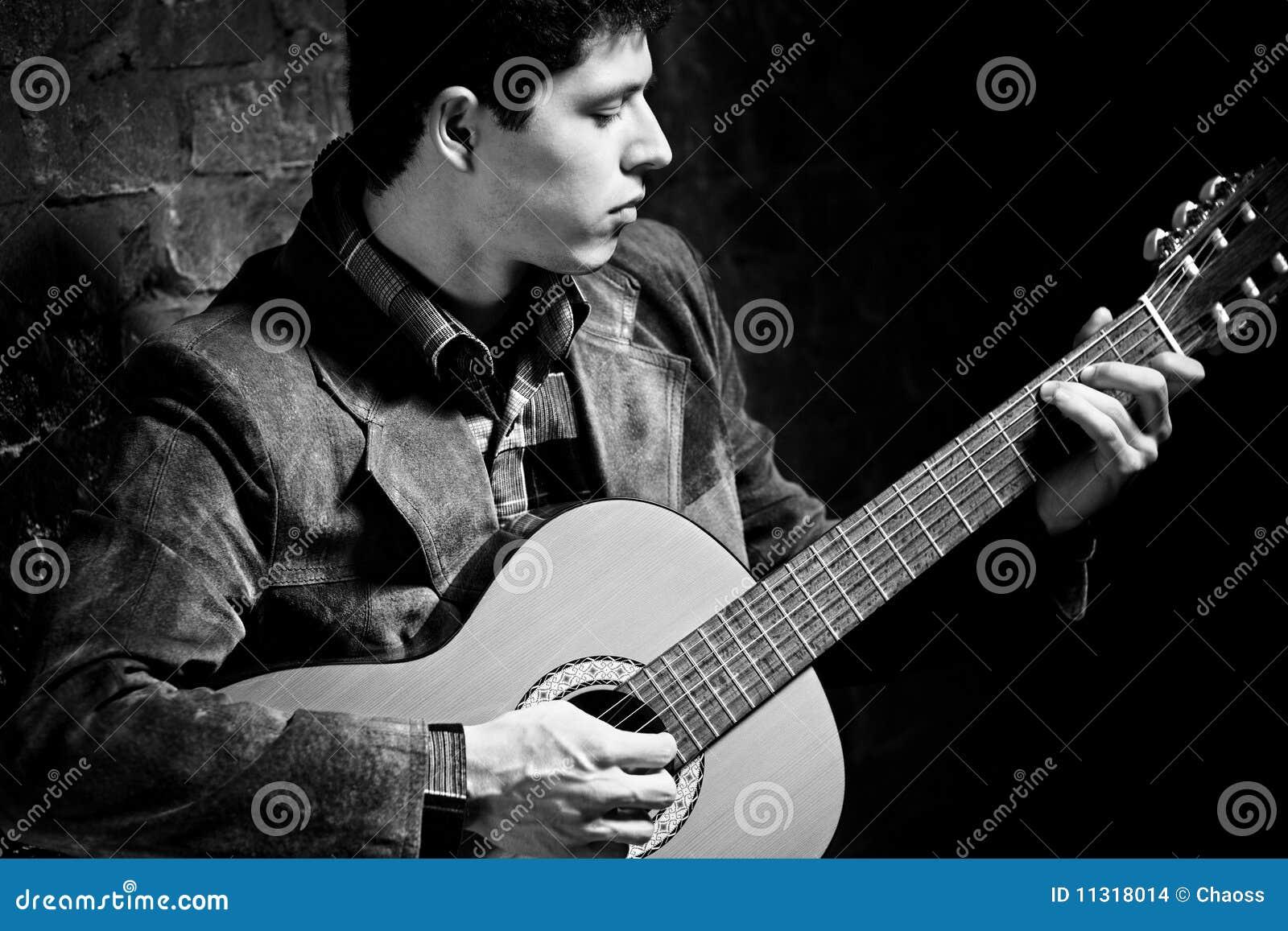Junger Mann, der auf Gitarre spielt