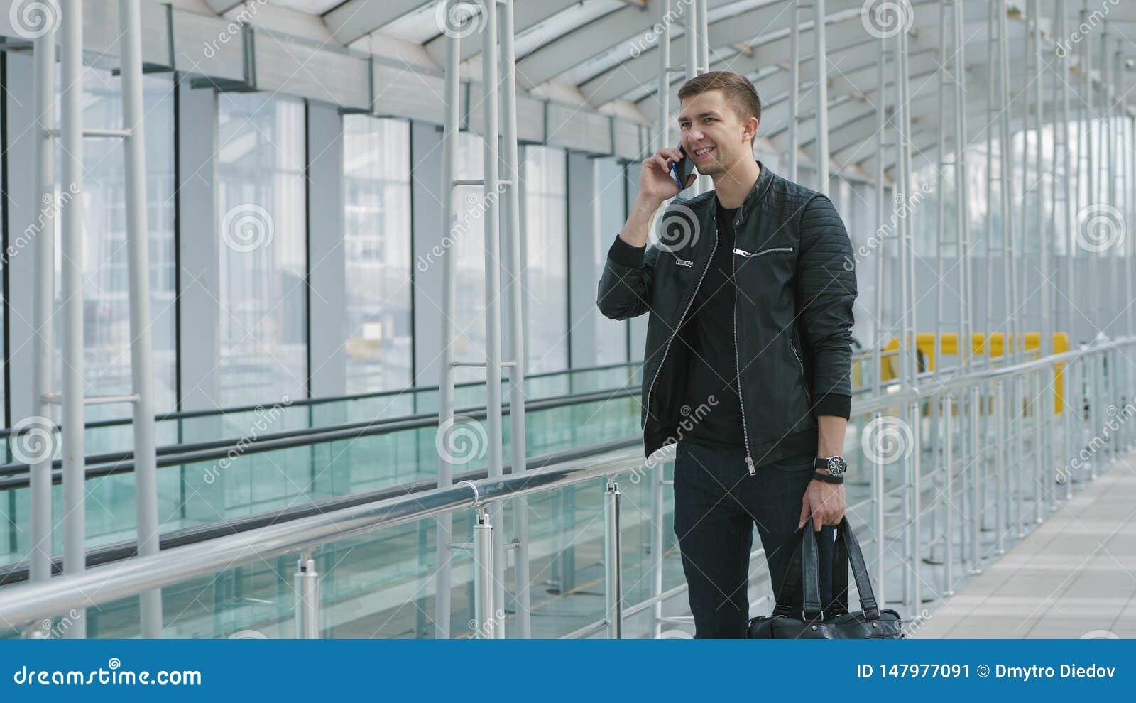Junger Mann, der auf Smartphone spricht