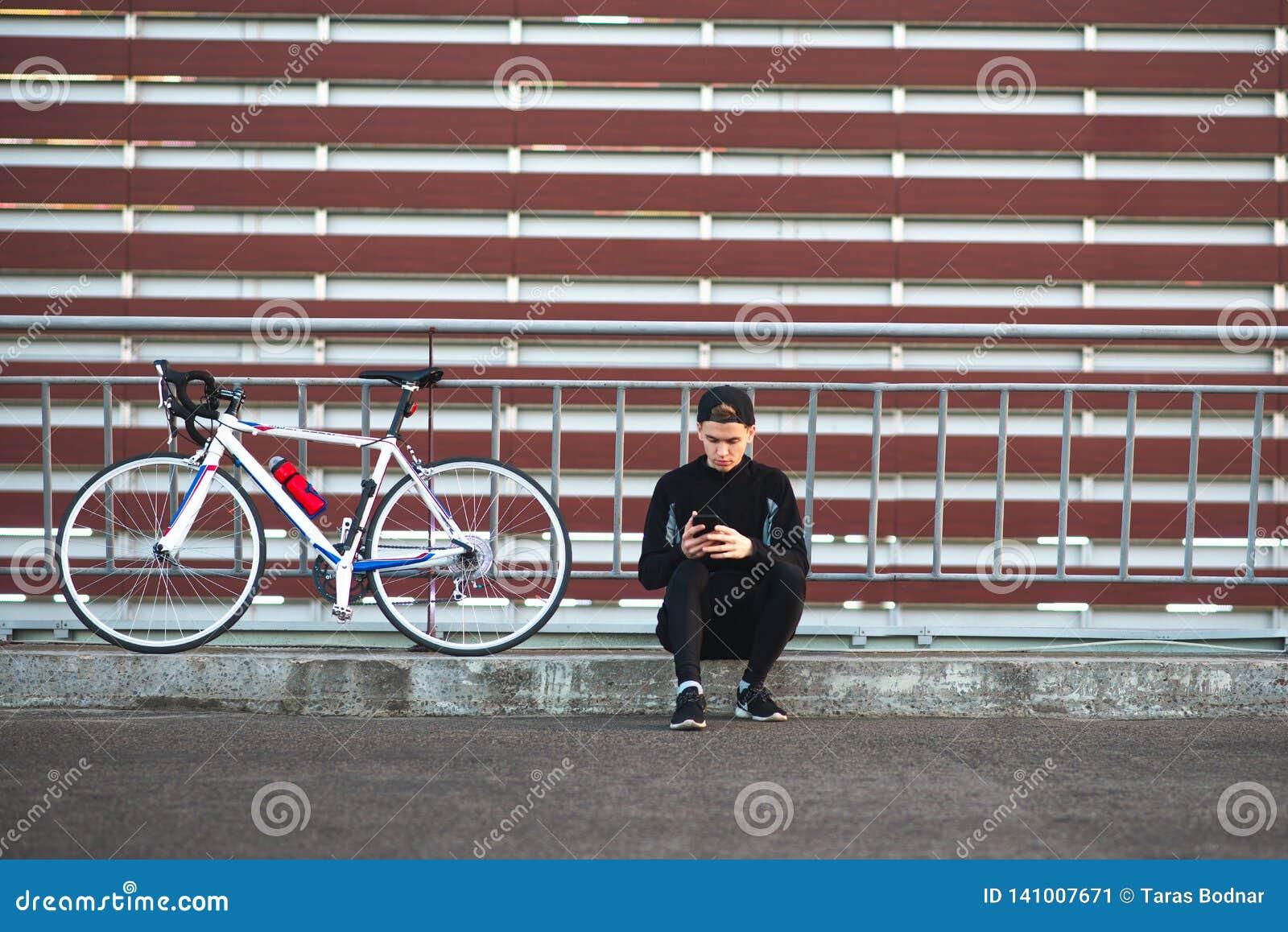Junger Mann, der in einem dunklen Kleid trägt ein Fahrrad und verwendet einen Smartphone auf dem Hintergrund einer gestreiften Bu