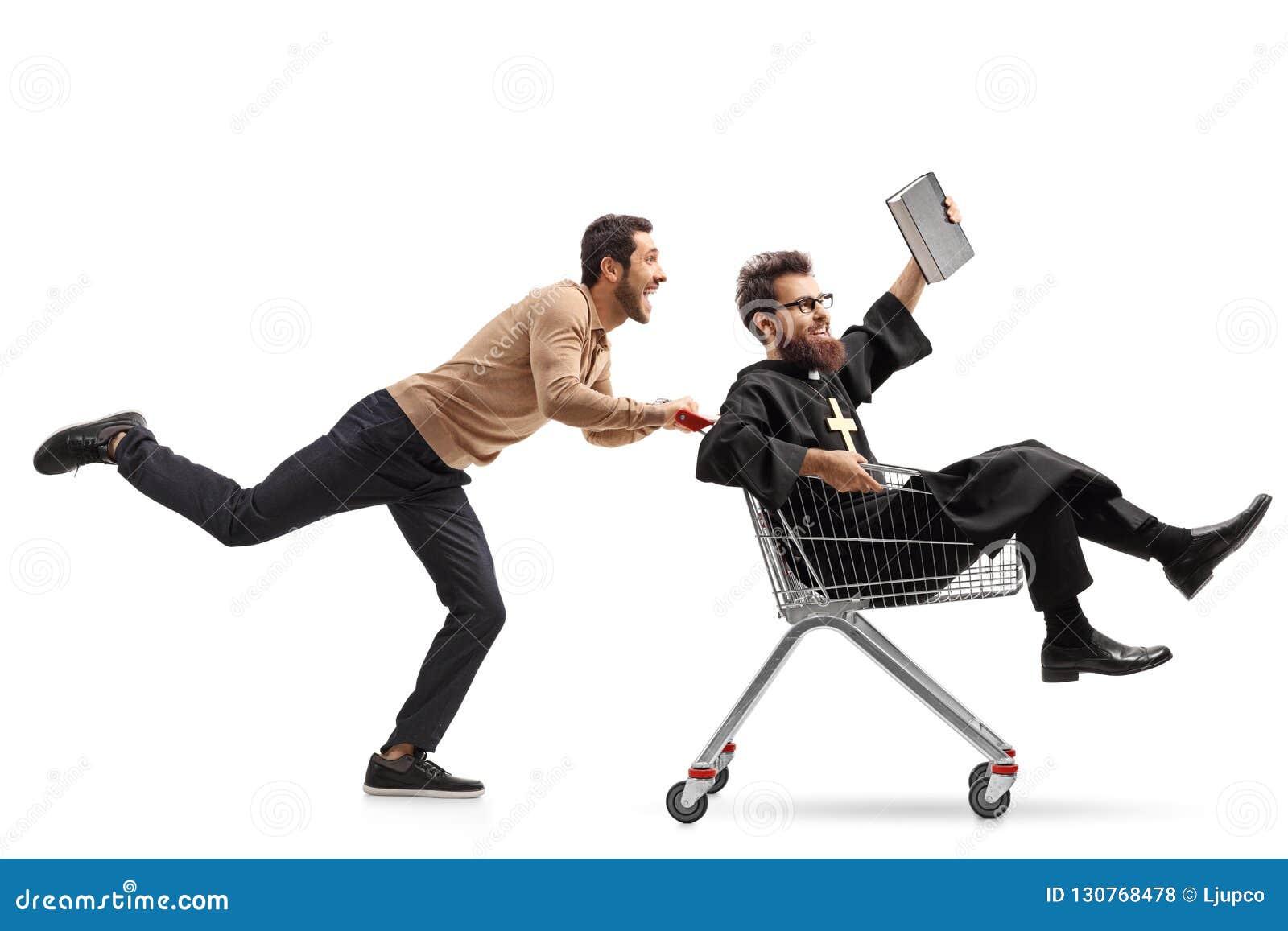 Junger Mann, der einen Priester in einem Einkaufswagen drückt