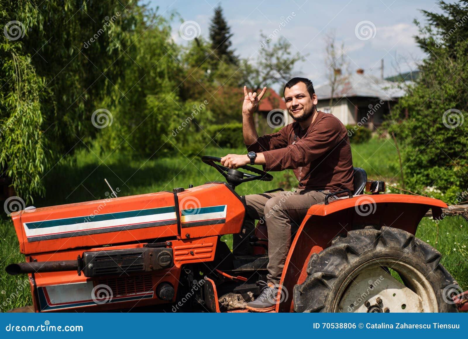 Junger Mann, der einen Traktor fährt