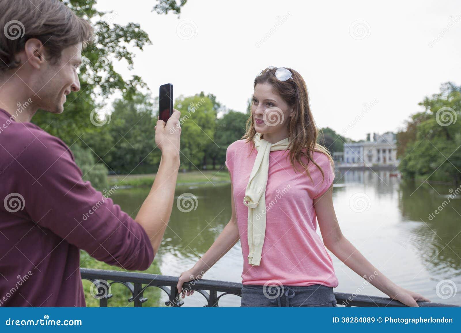 Junger Mann, Der Frau Durch Handy Am Seeufer Fotografiert
