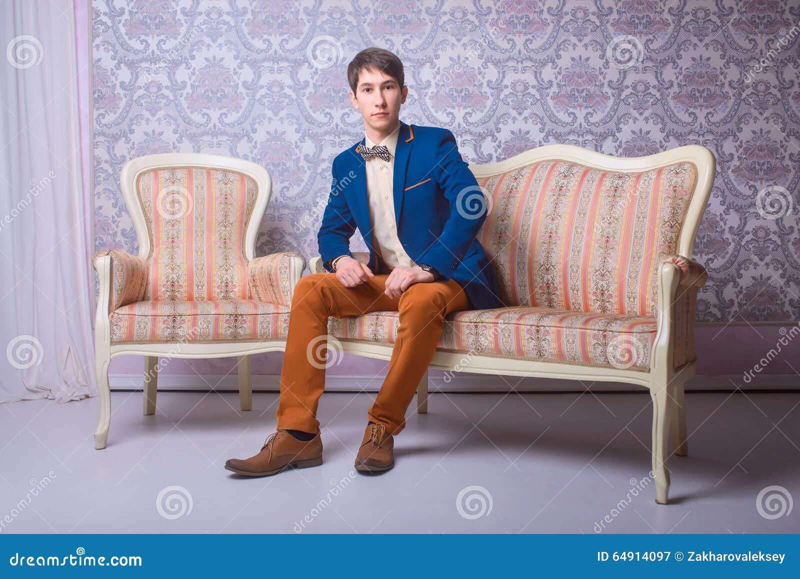 junger mann in der klassischen klage sitzt auf der couch stockbild bild von person gesch ft. Black Bedroom Furniture Sets. Home Design Ideas