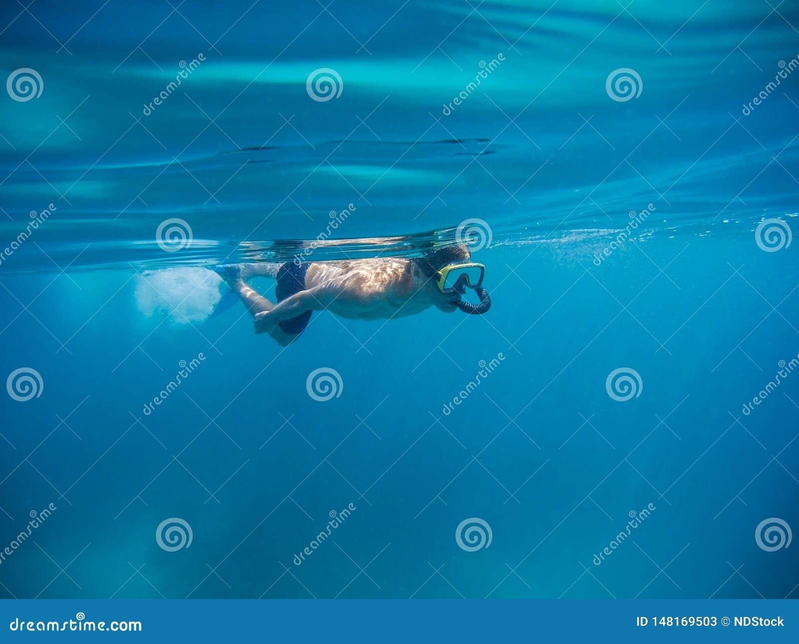 Junger Mann, der mit Maske und Flossen im klaren blauen Wasser schwimmt und schnorchelt